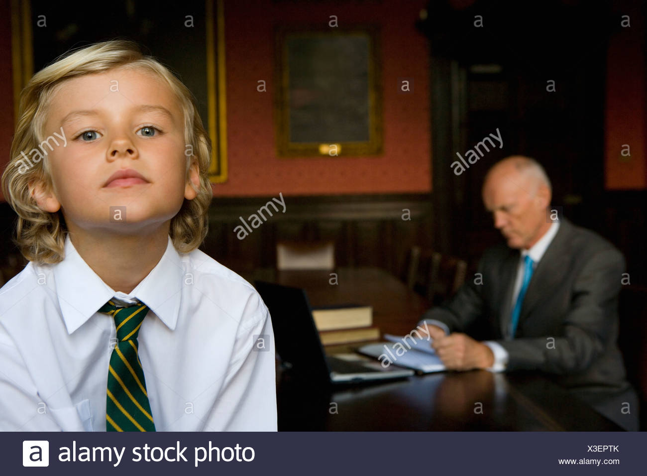 Boy (5-7) in office with father at desk in background Stock Photo