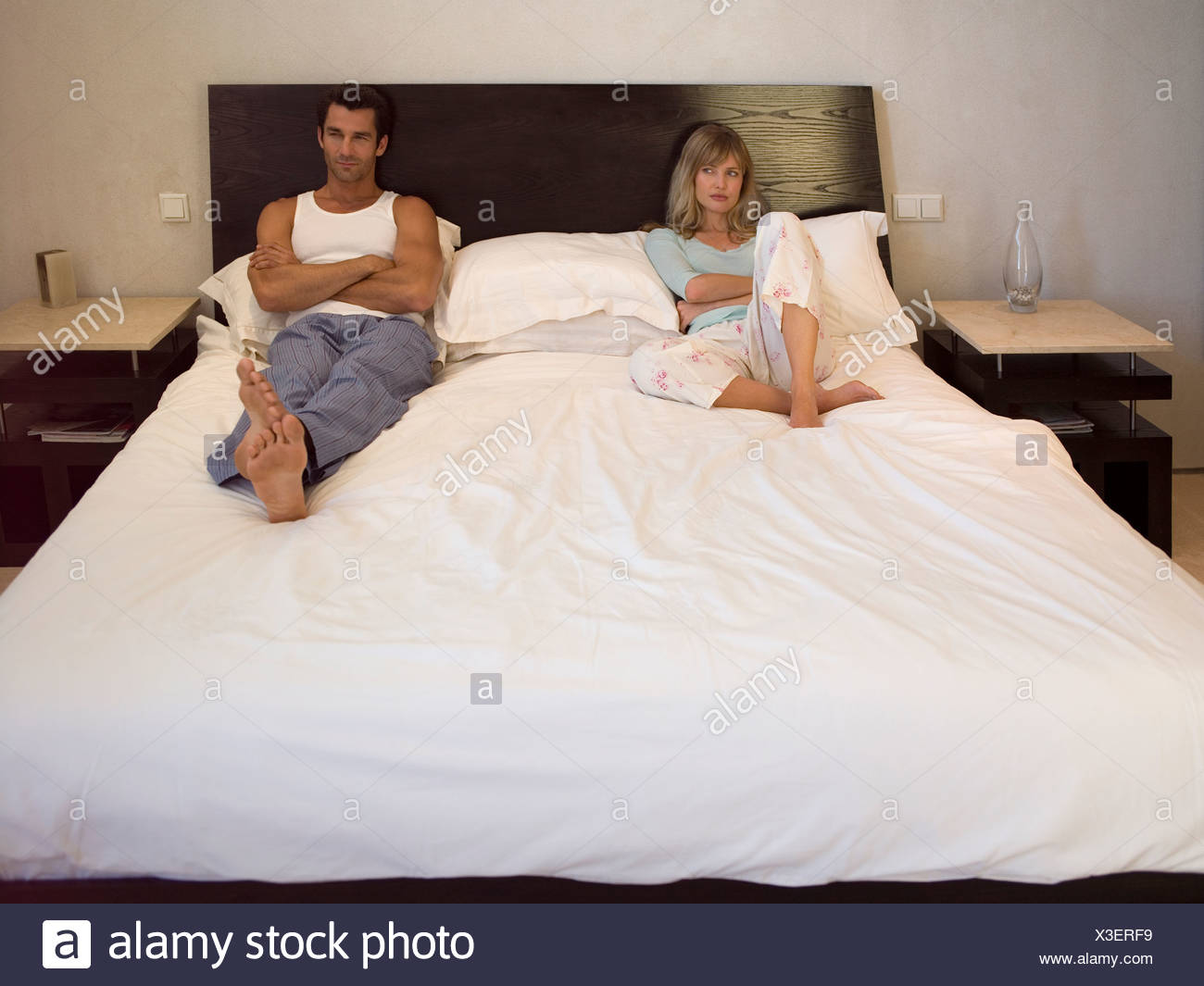 Couple sitting on the bed - Stock Image