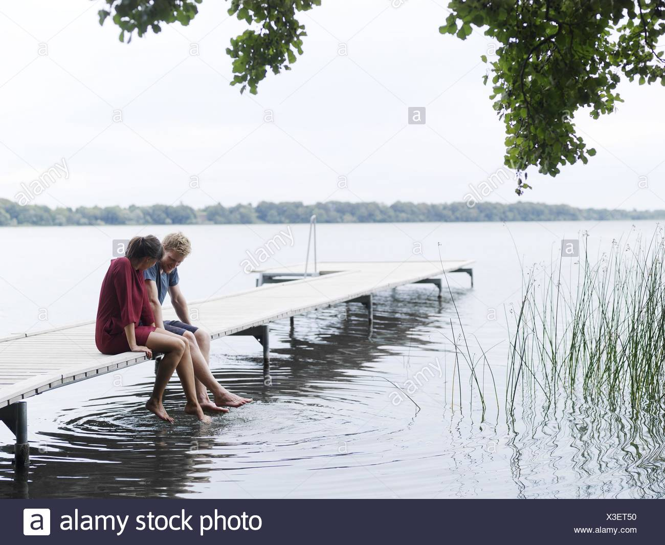 Couple sitting on pier side by side dipping toes in water, Copenhagen, Denmark - Stock Image