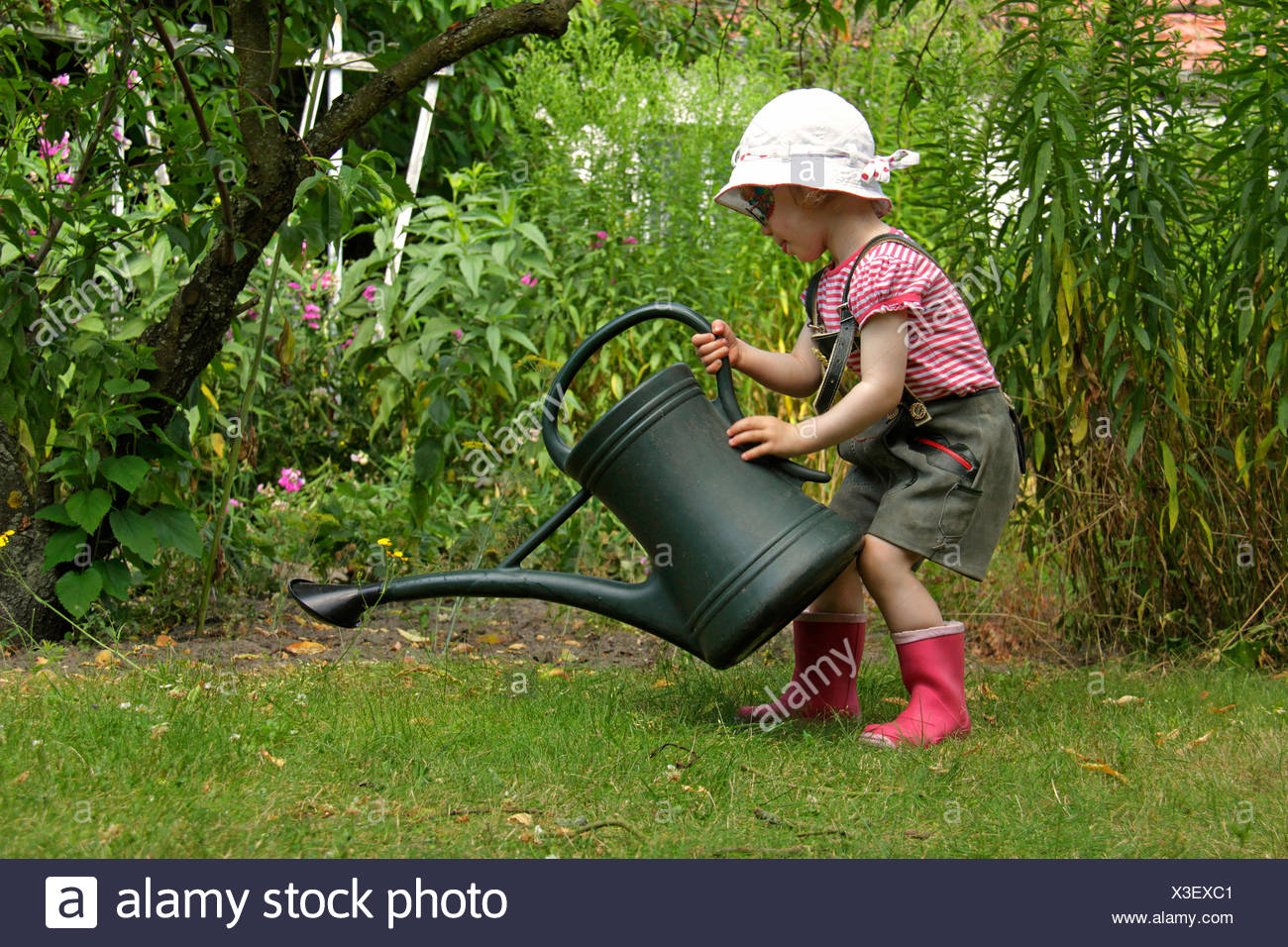 little girl in lederhosen playing in the garden with a watering can, Germany - Stock Image