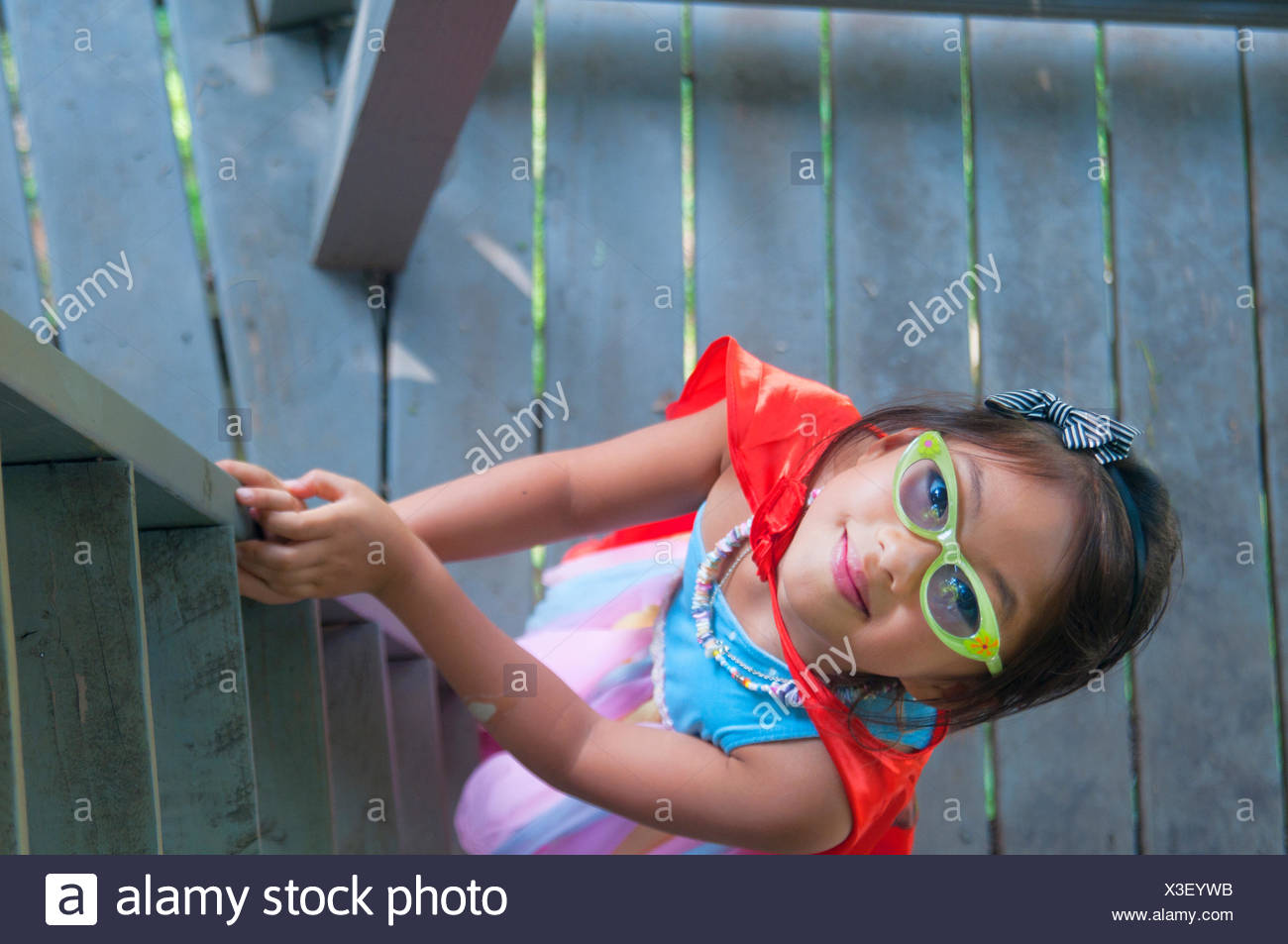 Young girl wearing cape, climbing wooden steps, high angle view - Stock Image