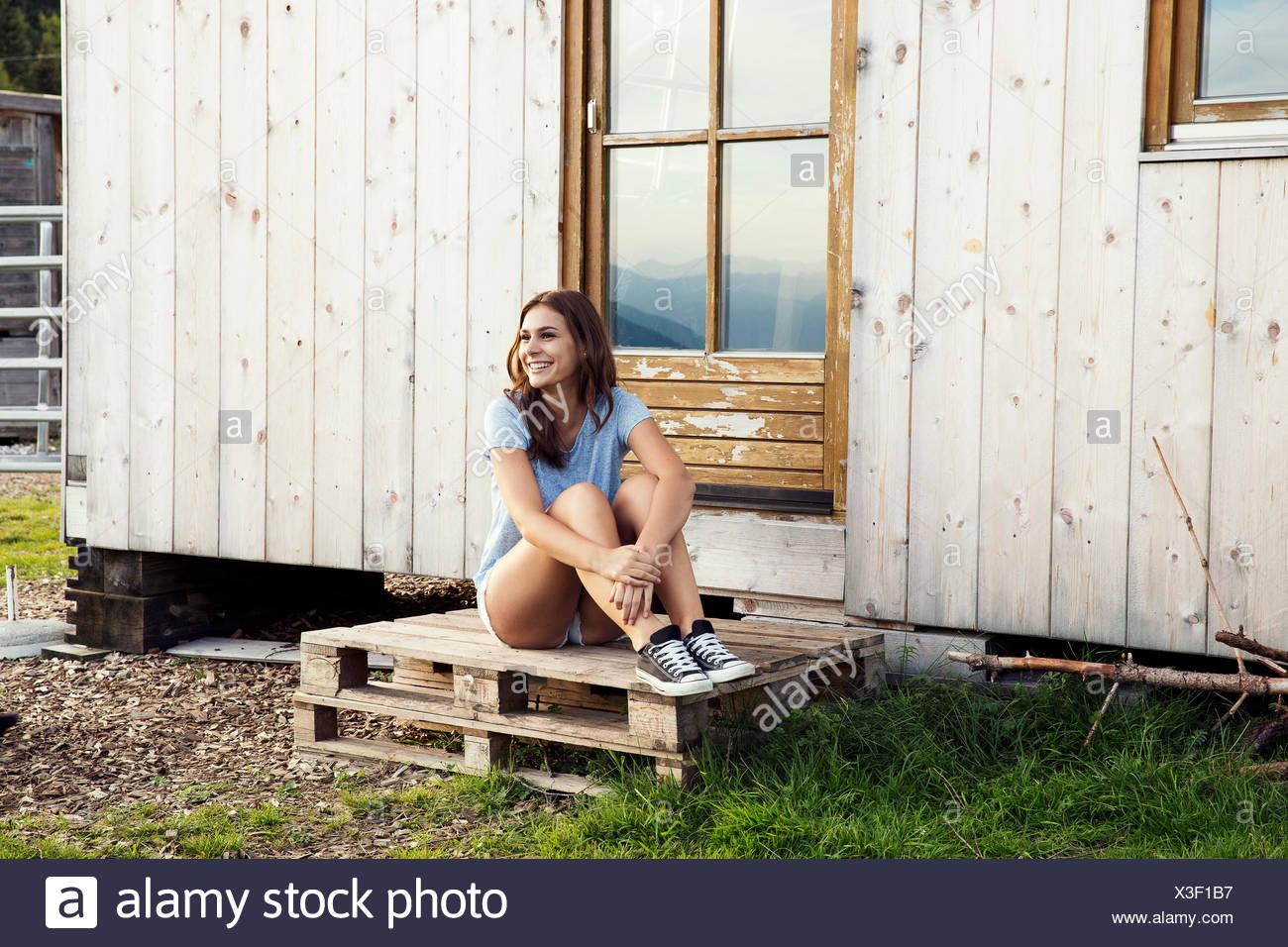 0f9f4e12d Young woman sitting on pallets outside chalet, Sattelbergalm, Tirol, Austria