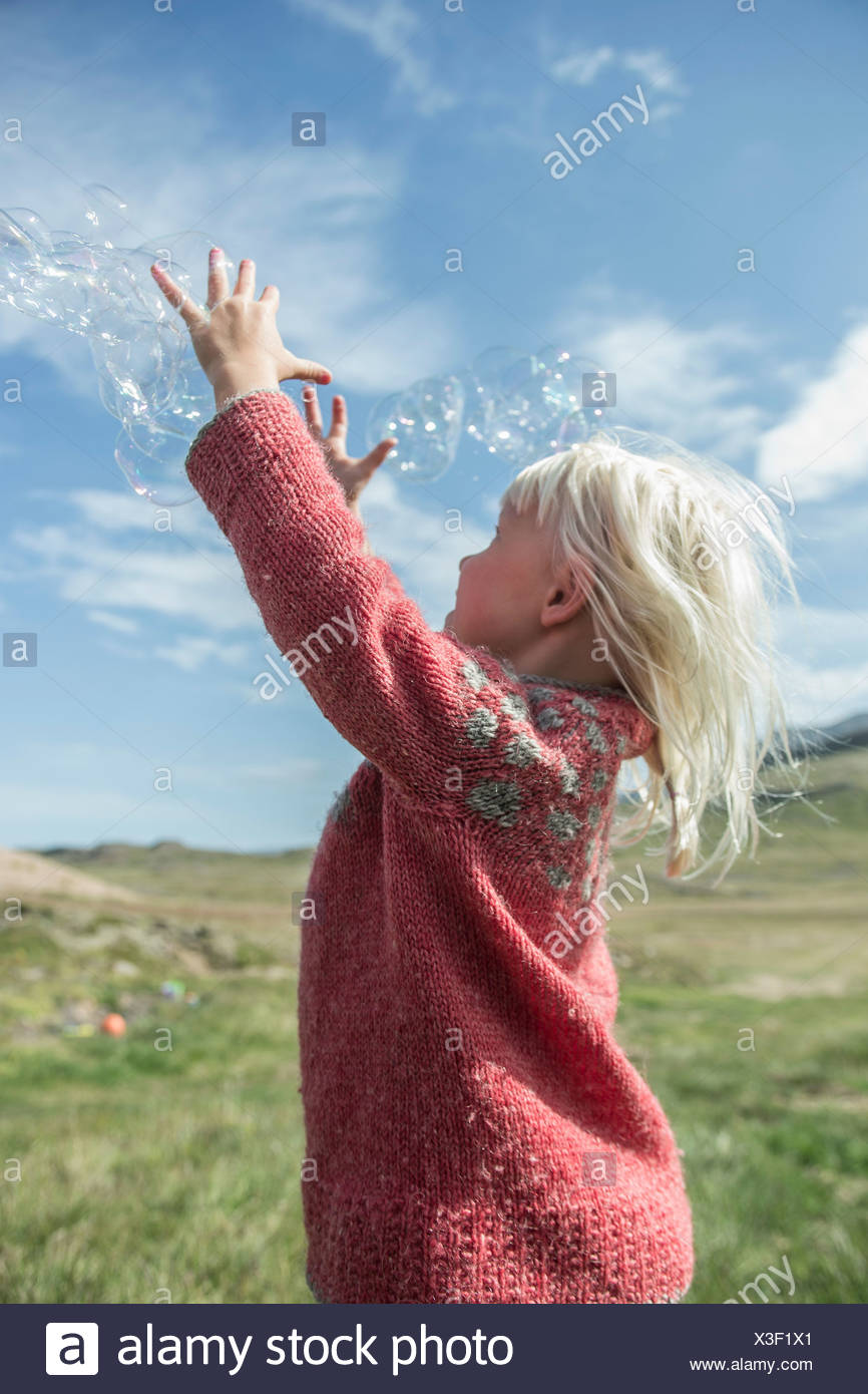 Young girl reaching to catch bubbles - Stock Image