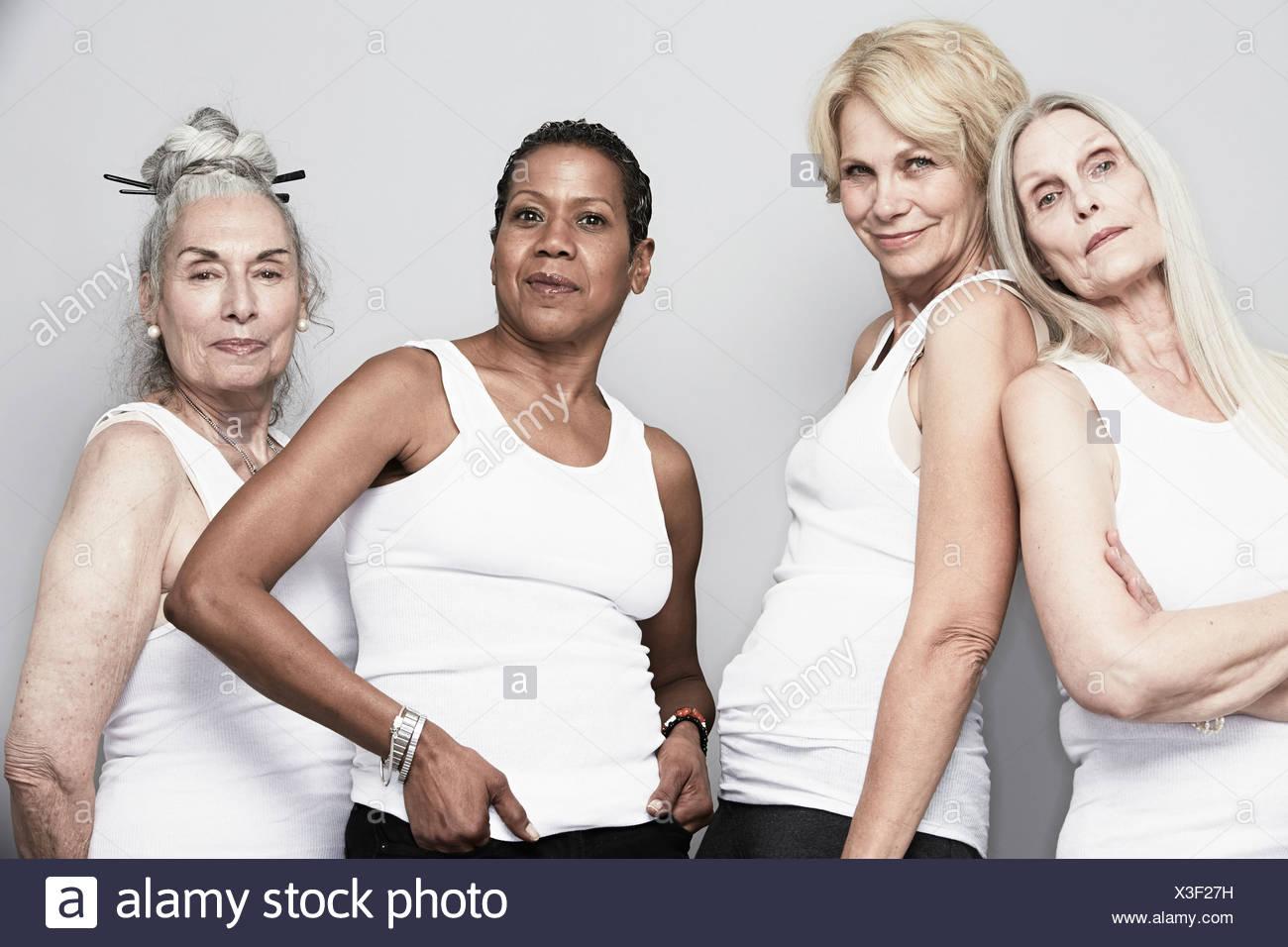 Studio portrait of senior women friends posing for camera - Stock Image
