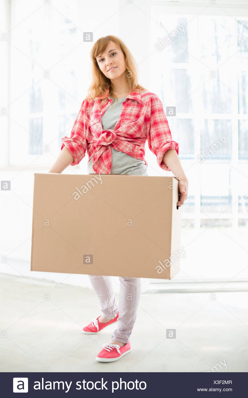 Full-length portrait of woman carrying cardboard box - Stock Image