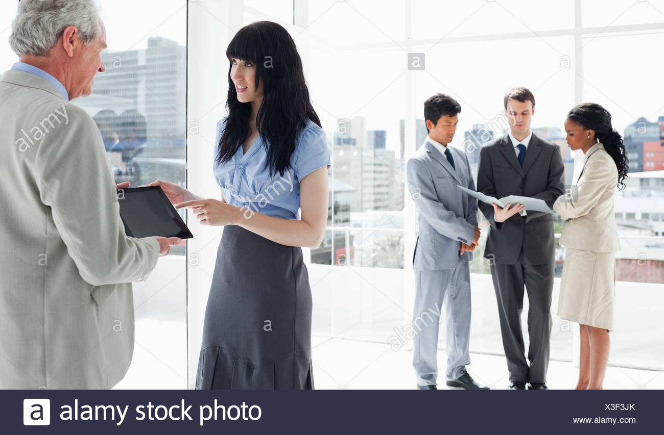 Serious business people looking at a tablet computer with the team near them Stock Photo