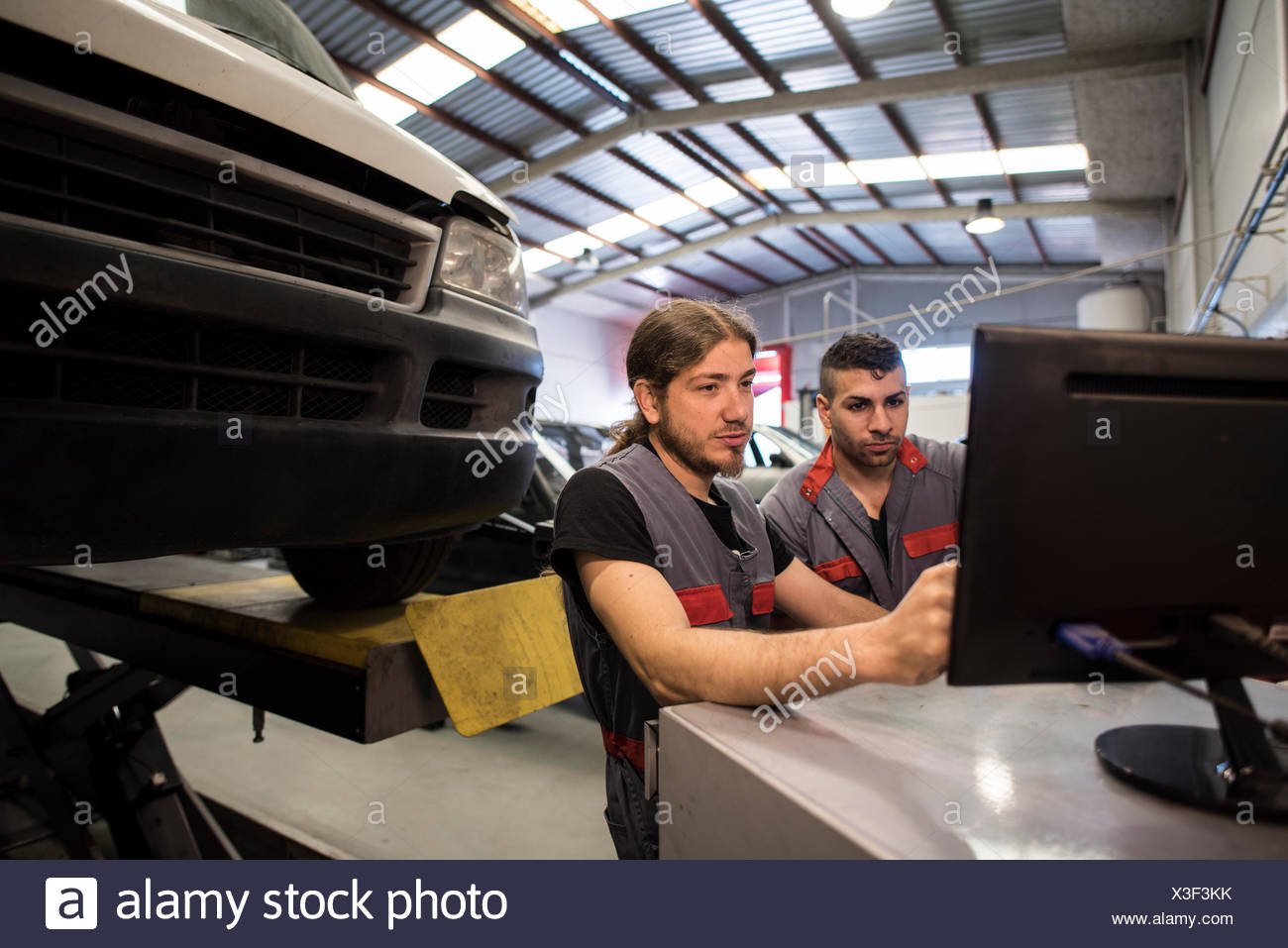 Mechanic calibrating wheels with computer and technology equipment - Stock Image