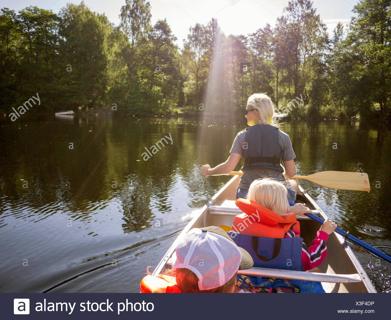 Mother, son (8-9) and daughter (6-7) navigating across lake in rowboat - Stock Image