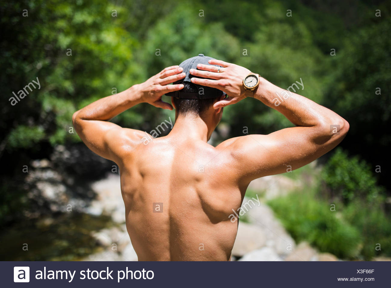 Back of shirtless young man wearing wrist watch Stock Photo
