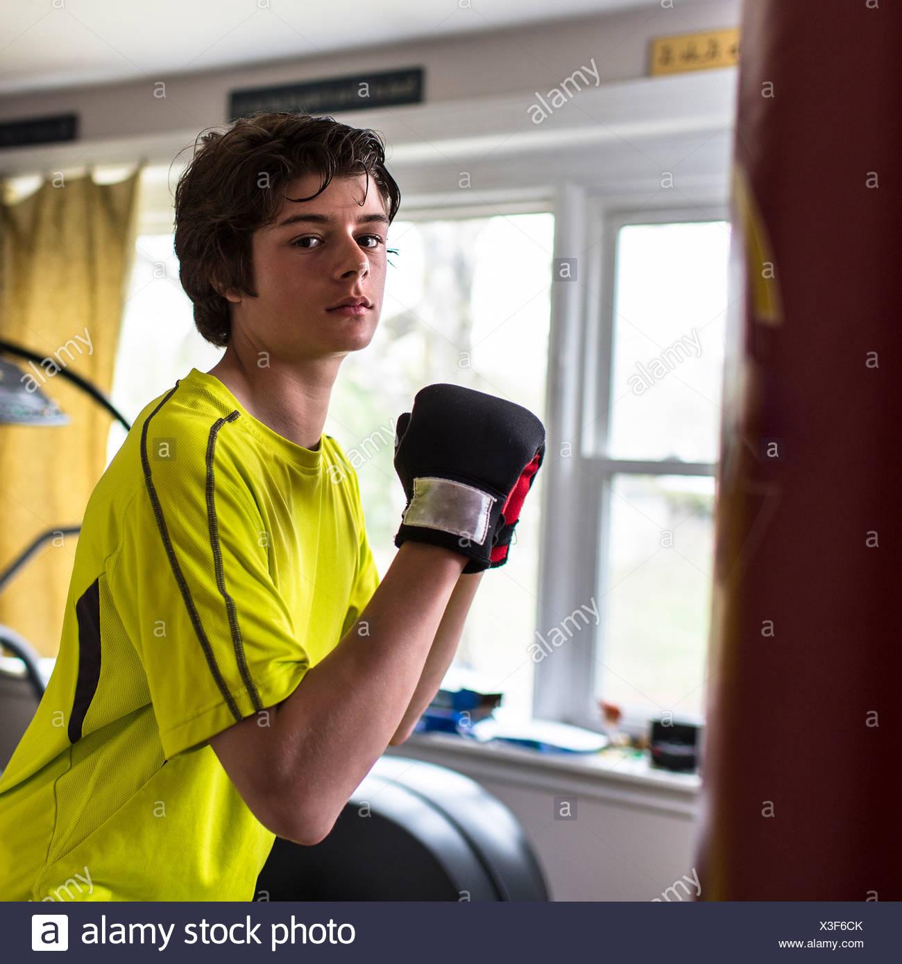 Teenage boy wearing boxing gloves - Stock Image