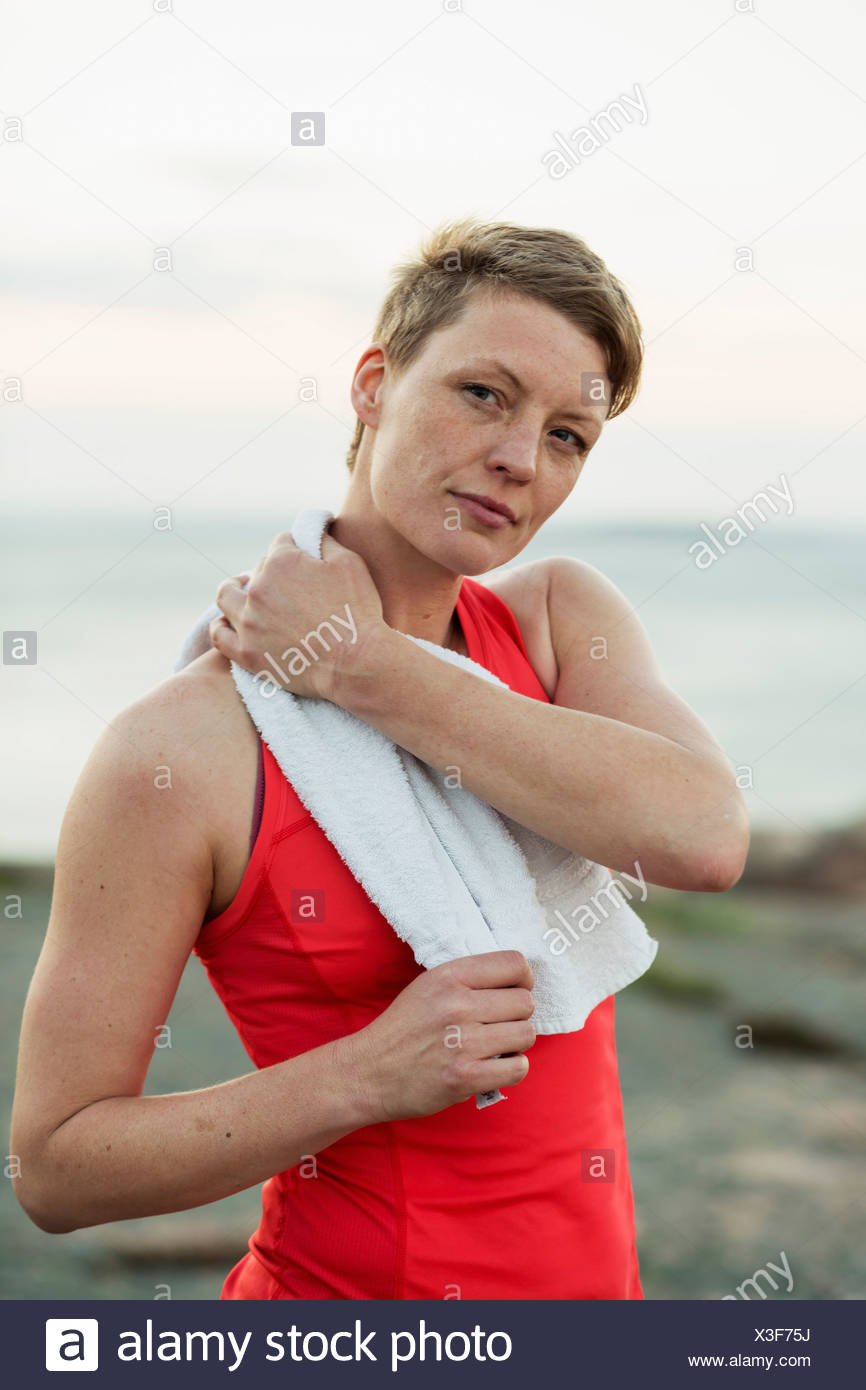 Portrait of sporty woman wiping sweat with towel outdoors Stock Photo