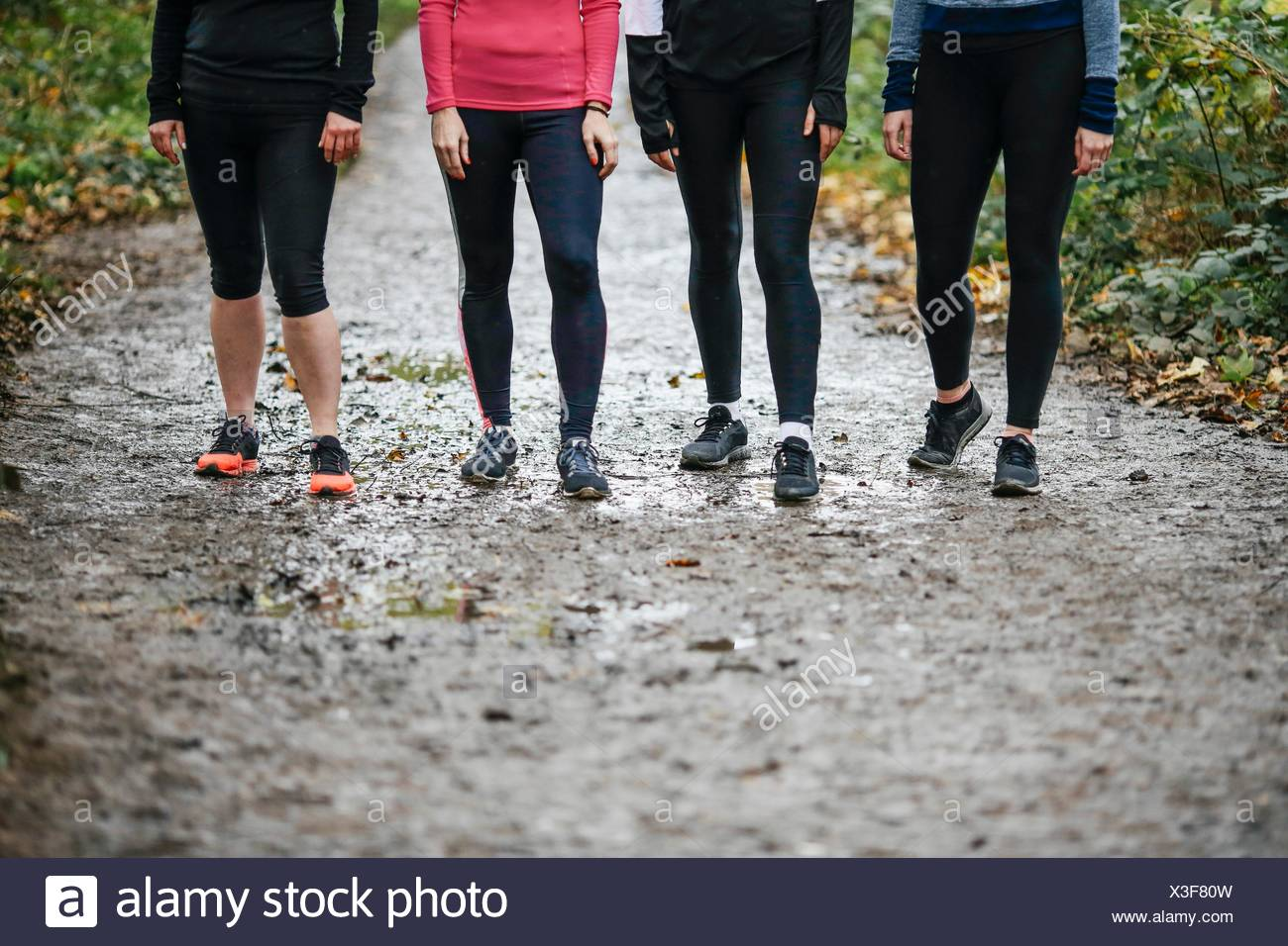 Waist down of teenage girl and women runners preparing to run in park - Stock Image