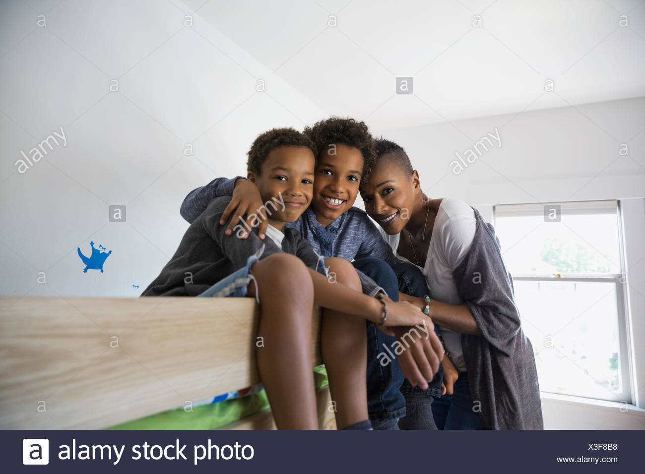 Portrait of smiling family on bunk bed - Stock Image