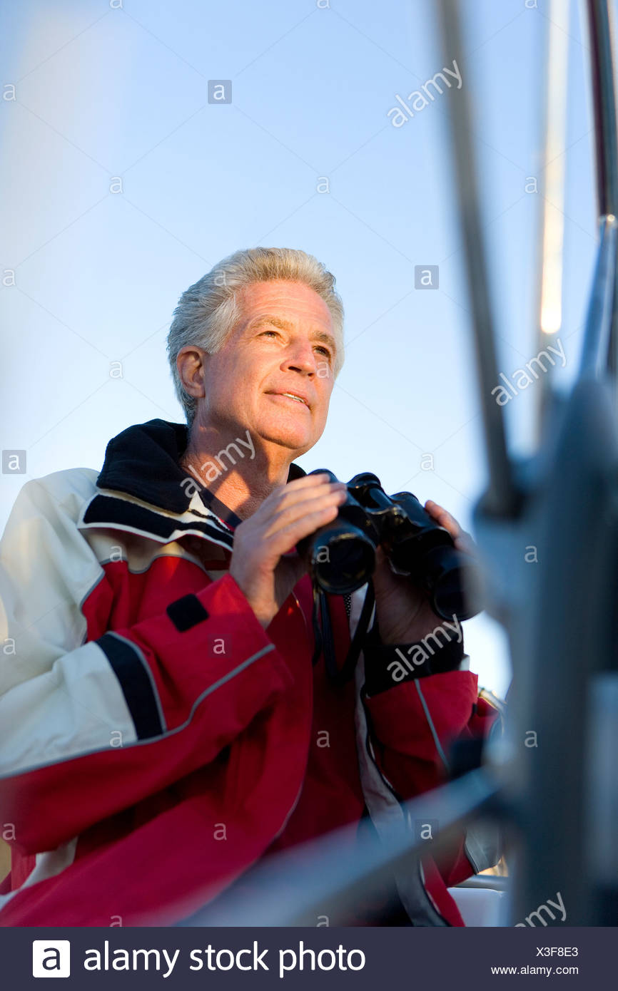 Mature man, in red waterproof jacket, standing on deck of yacht, holding pair of binoculars, smiling Stock Photo