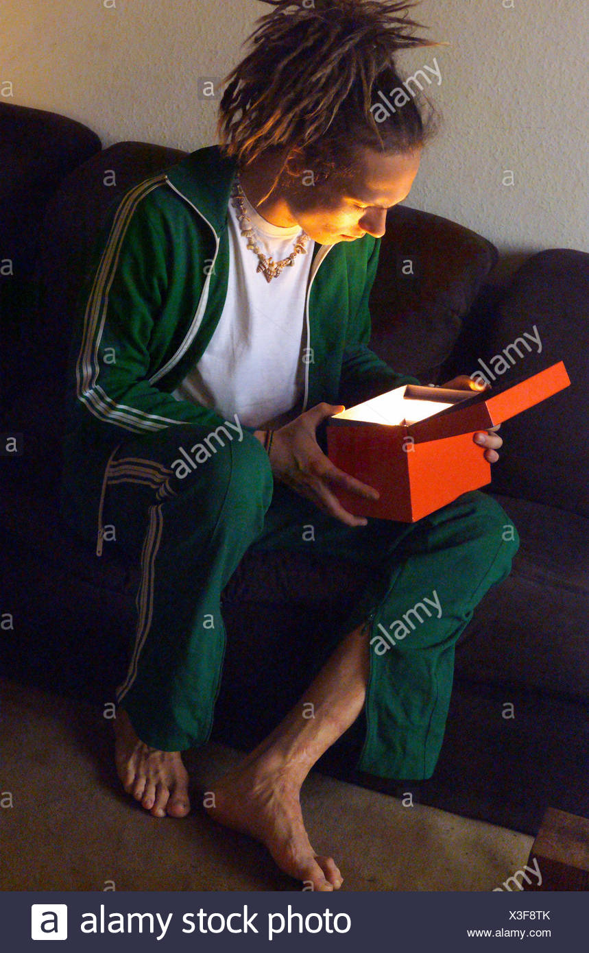Sofa, man, young, dreadlocks, view, box, light, Ti5, esotericism, occultism, occult, faith, hope, magic, mysticism, mystically, Mysteriously, oracle, Übersinnlichkeit, extrasensory, fascination, entrancedly, tracksuit, barefoot, hairstyle, disorderly - Stock Image