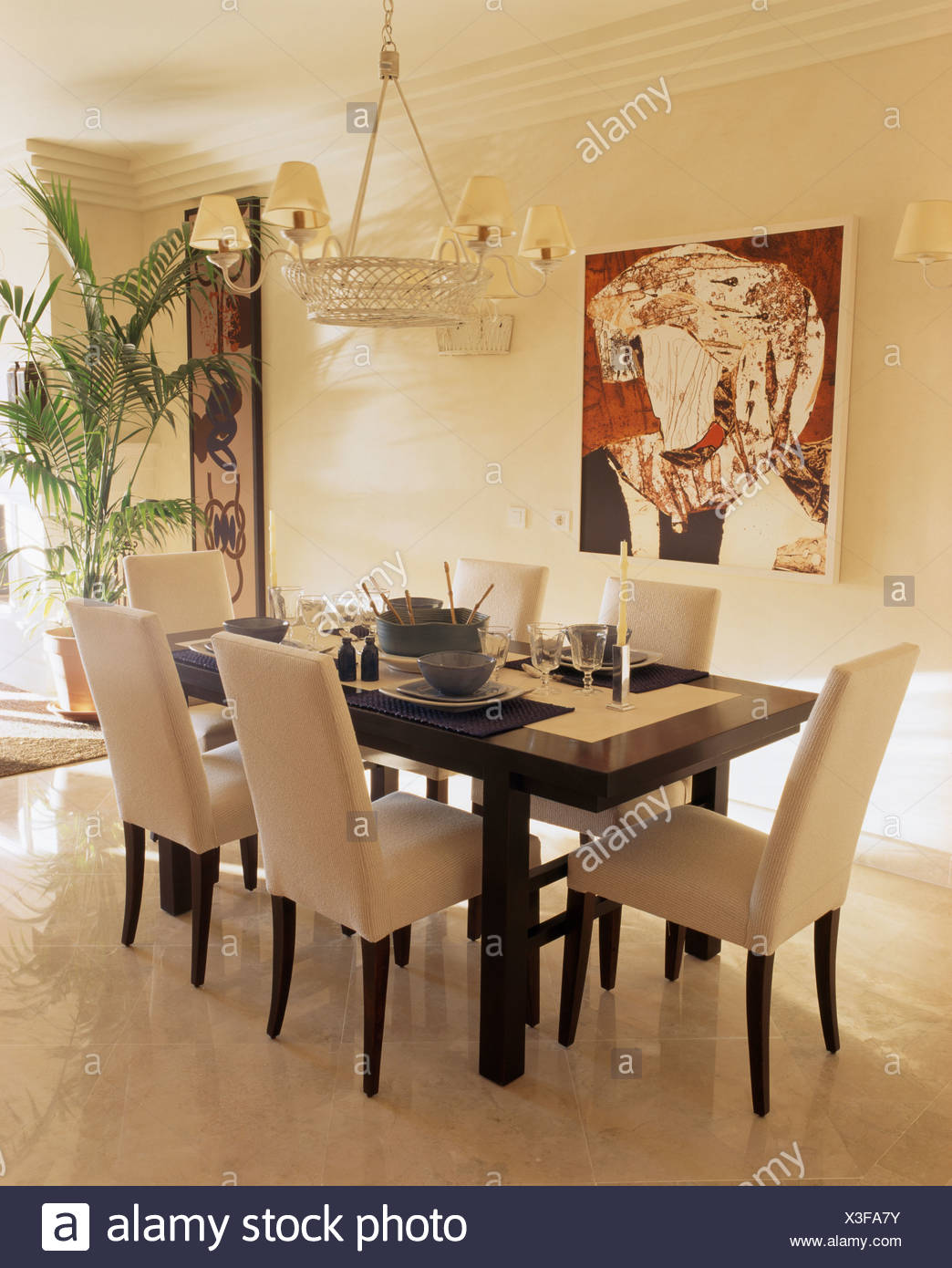 Tall-back cream upholstered chairs and black table in modern ...