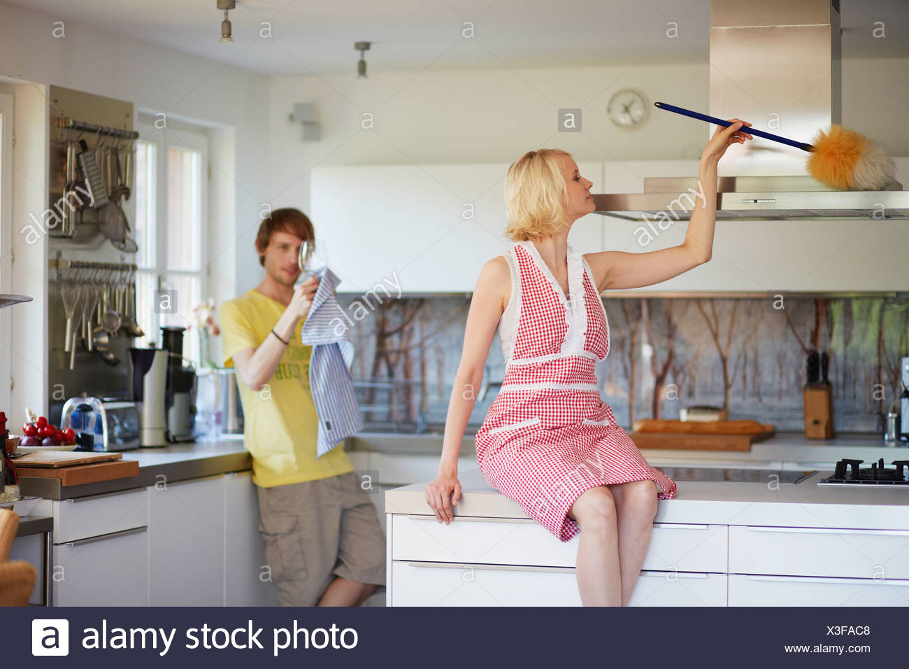 Couple cleaning together in kitchen - Stock Image