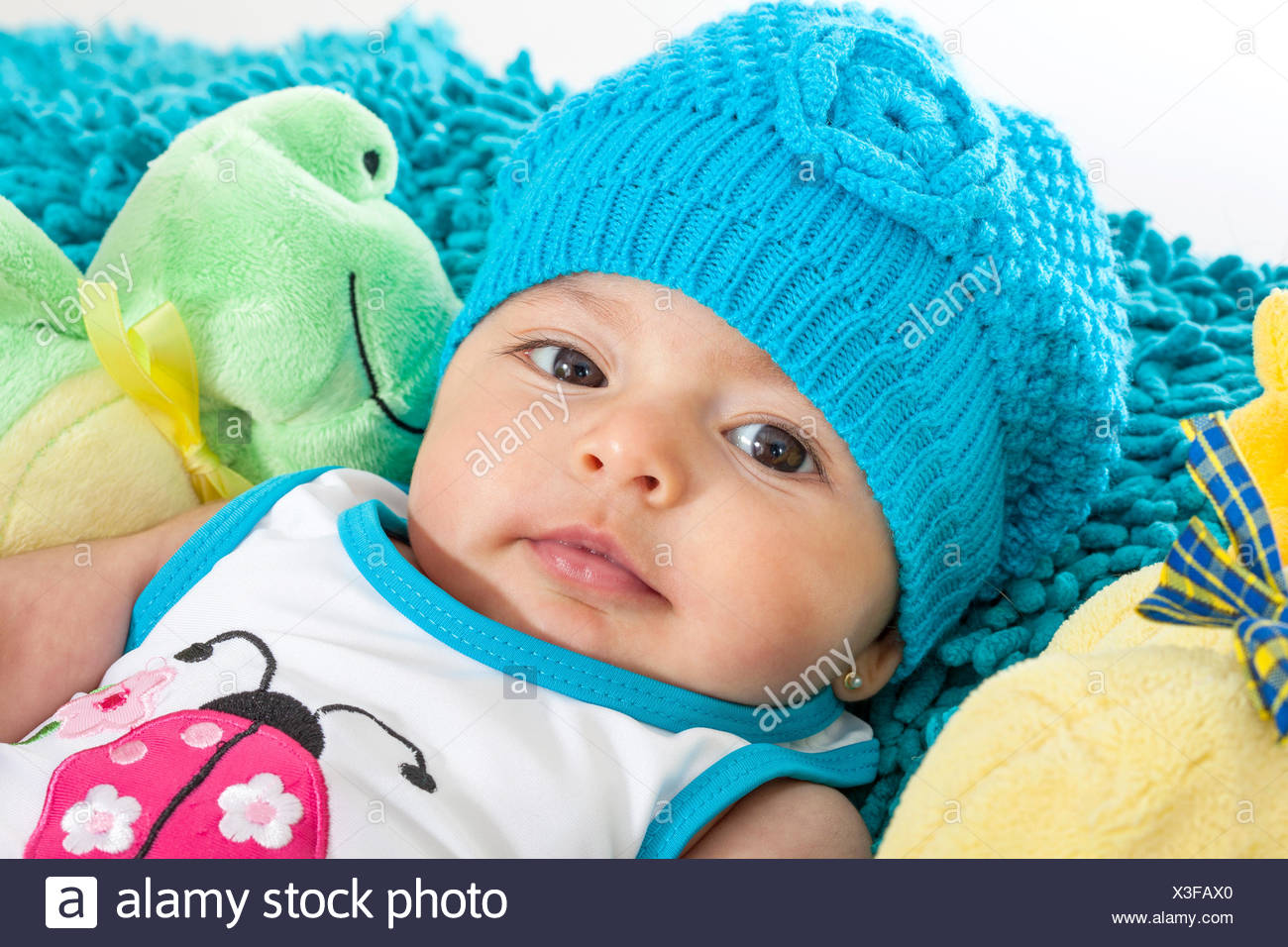 Four months old baby girl wearing a blue cap - Stock Image