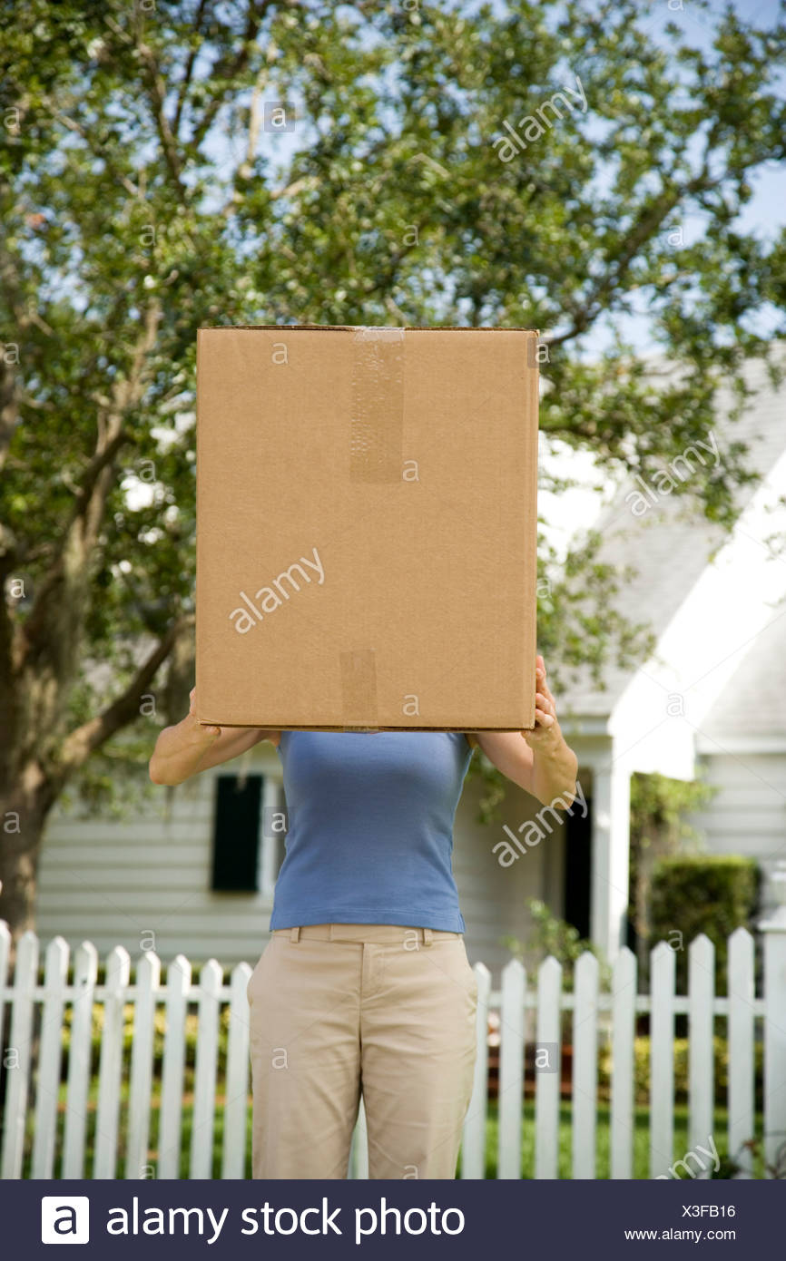 Woman moving house, carrying large packing box - Stock Image