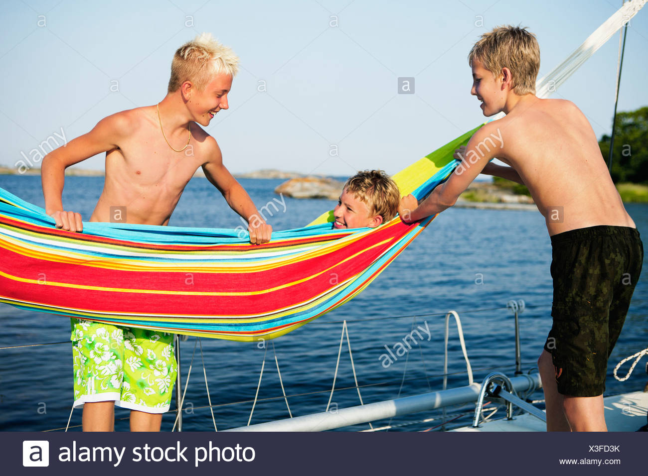 Three teenage boys (14-15,16-17) on boat deck, on of them lying in hammock - Stock Image