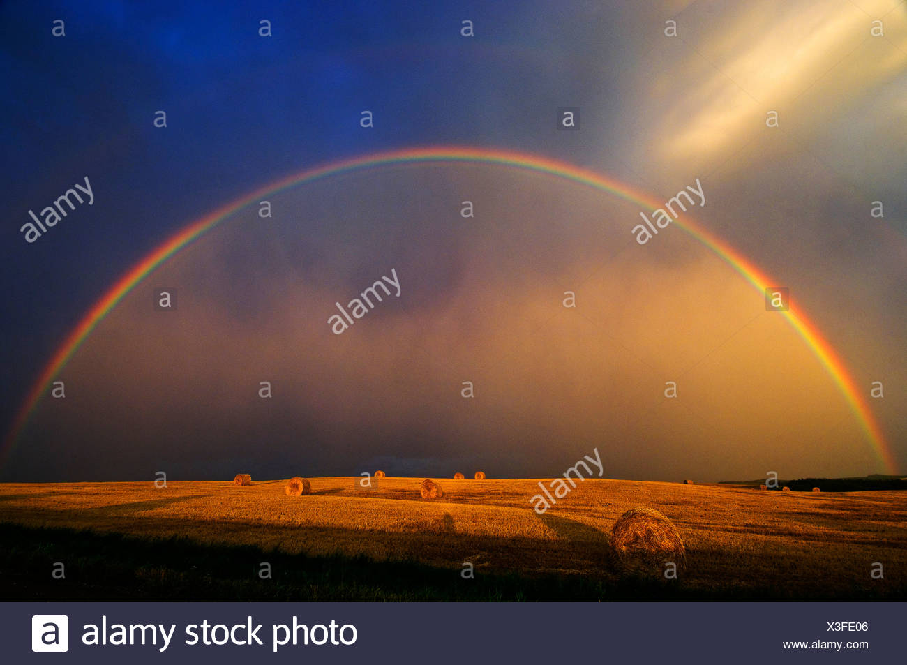Rainbow and bales after prairie storm at sunset near Cypress River, Manitoba, Canada. - Stock Image