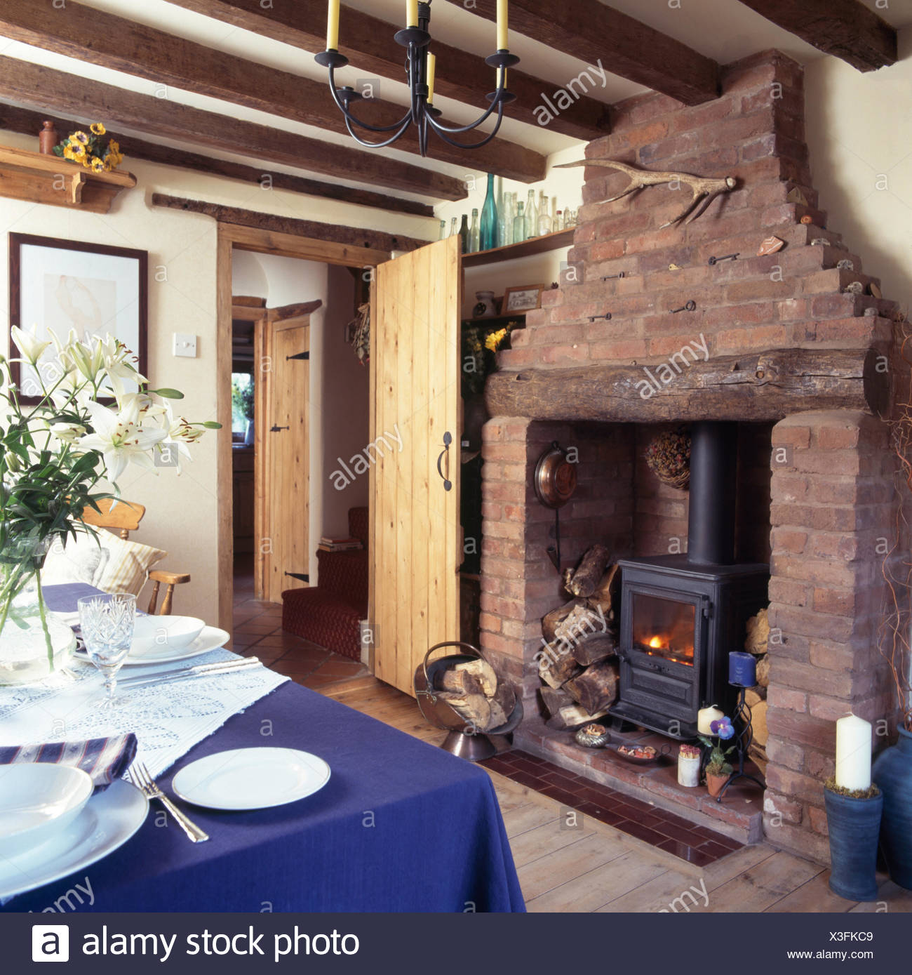 Wood Burning Stove In Exposed Brick Fireplace A Cottage Dining Room With Blue Cloth On Table Set For Lunch