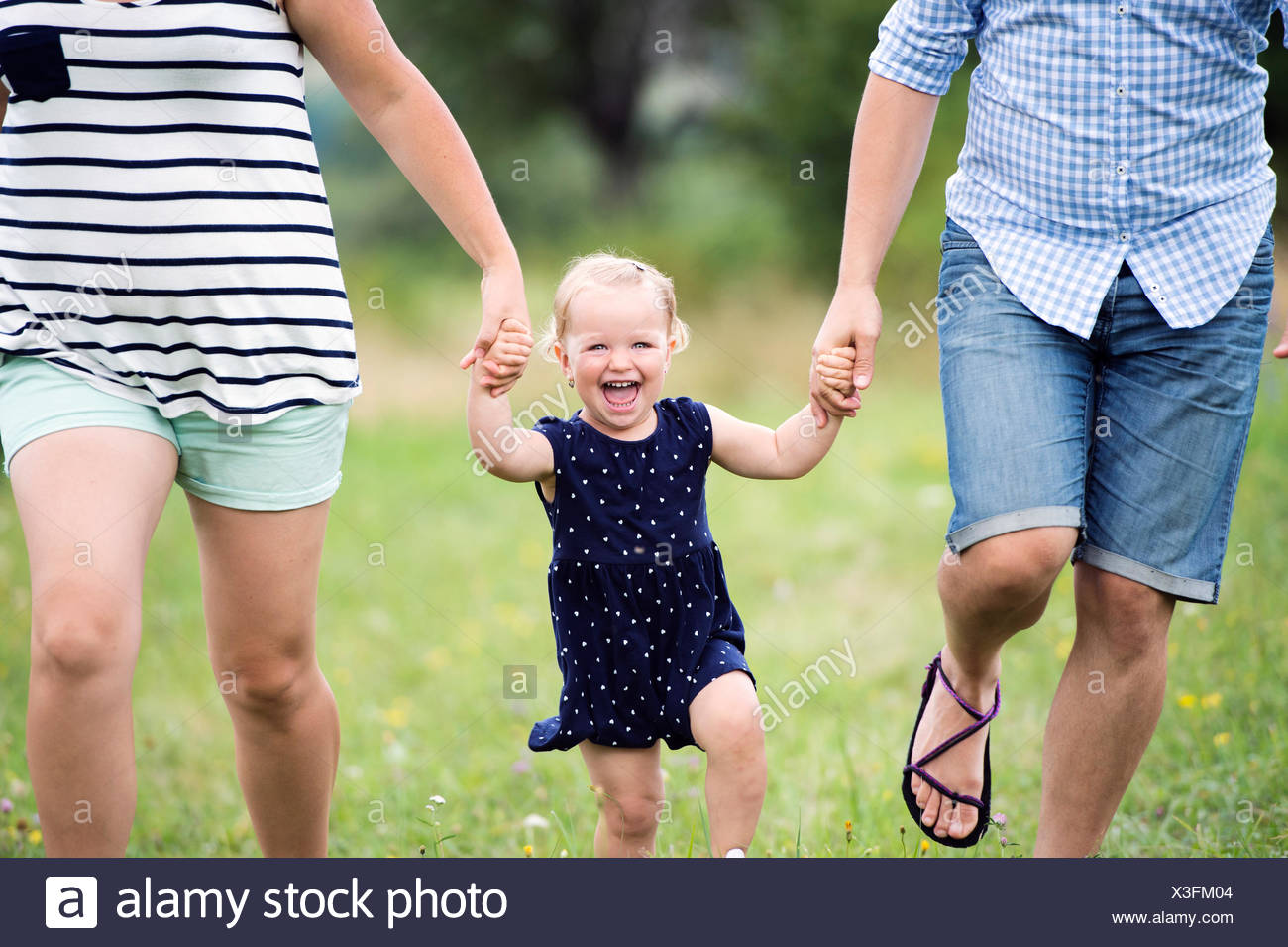 Laughing toddler girl holding hands of parents while running - Stock Image