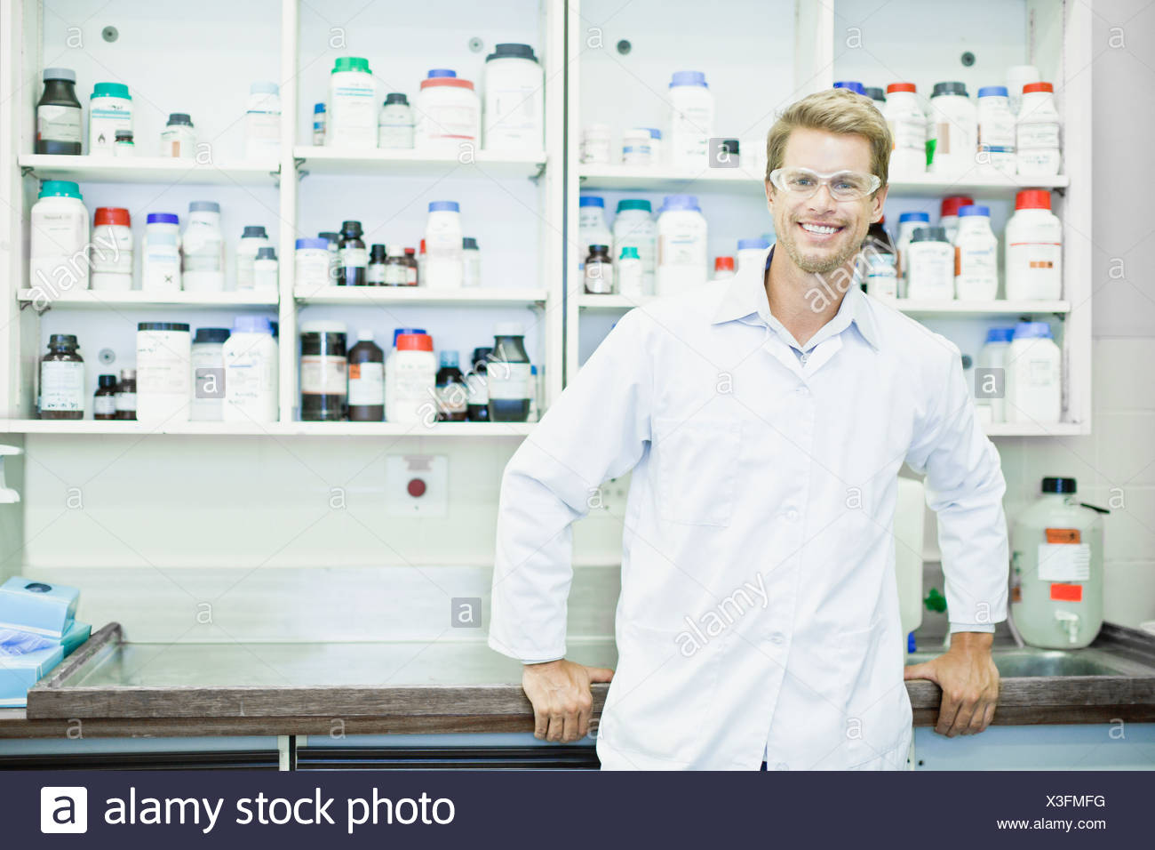 Scientist wearing goggles in lab - Stock Image
