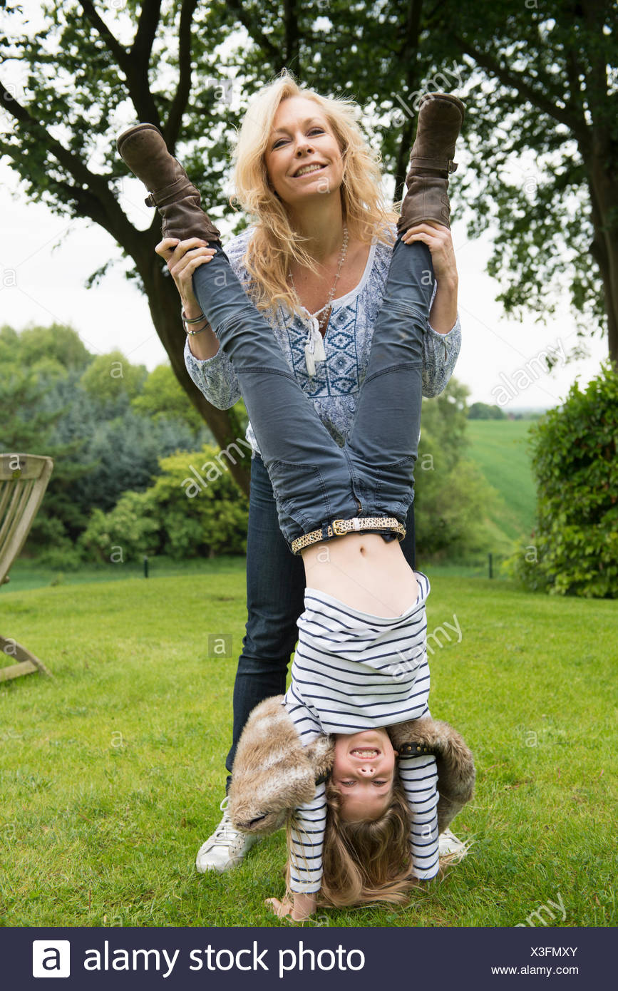 Mother holding daughter doing handstand - Stock Image
