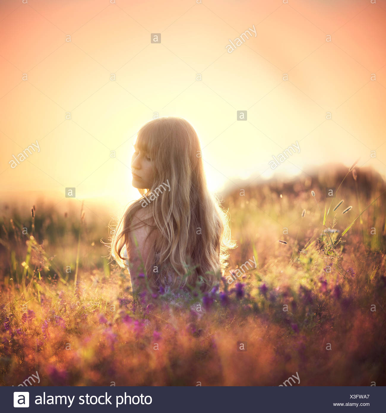 Woman looking over her shoulder in field - Stock Image