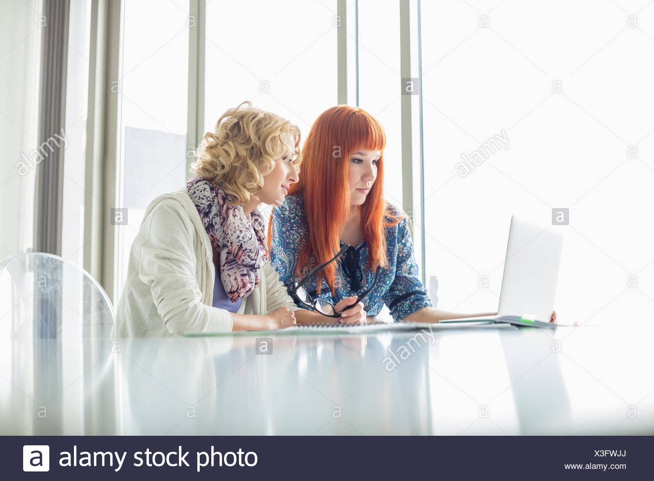 Creative businesswomen working on laptop together in office - Stock Image