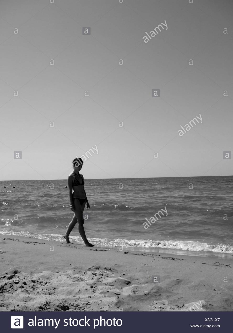 Young Woman In Bikini Walking At Shore Against Sky - Stock Image