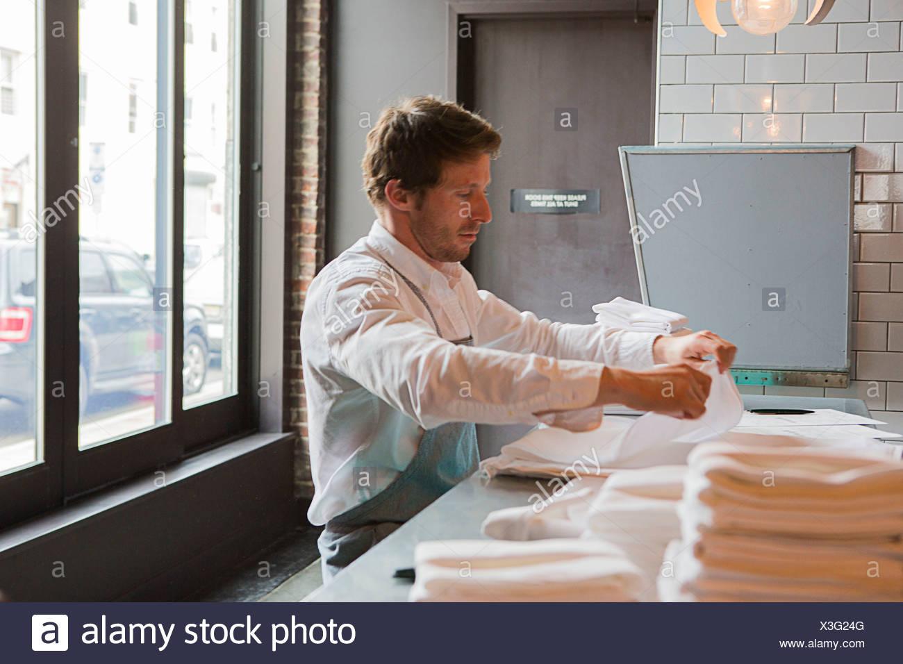 Chef preparing napkins in restaurant - Stock Image