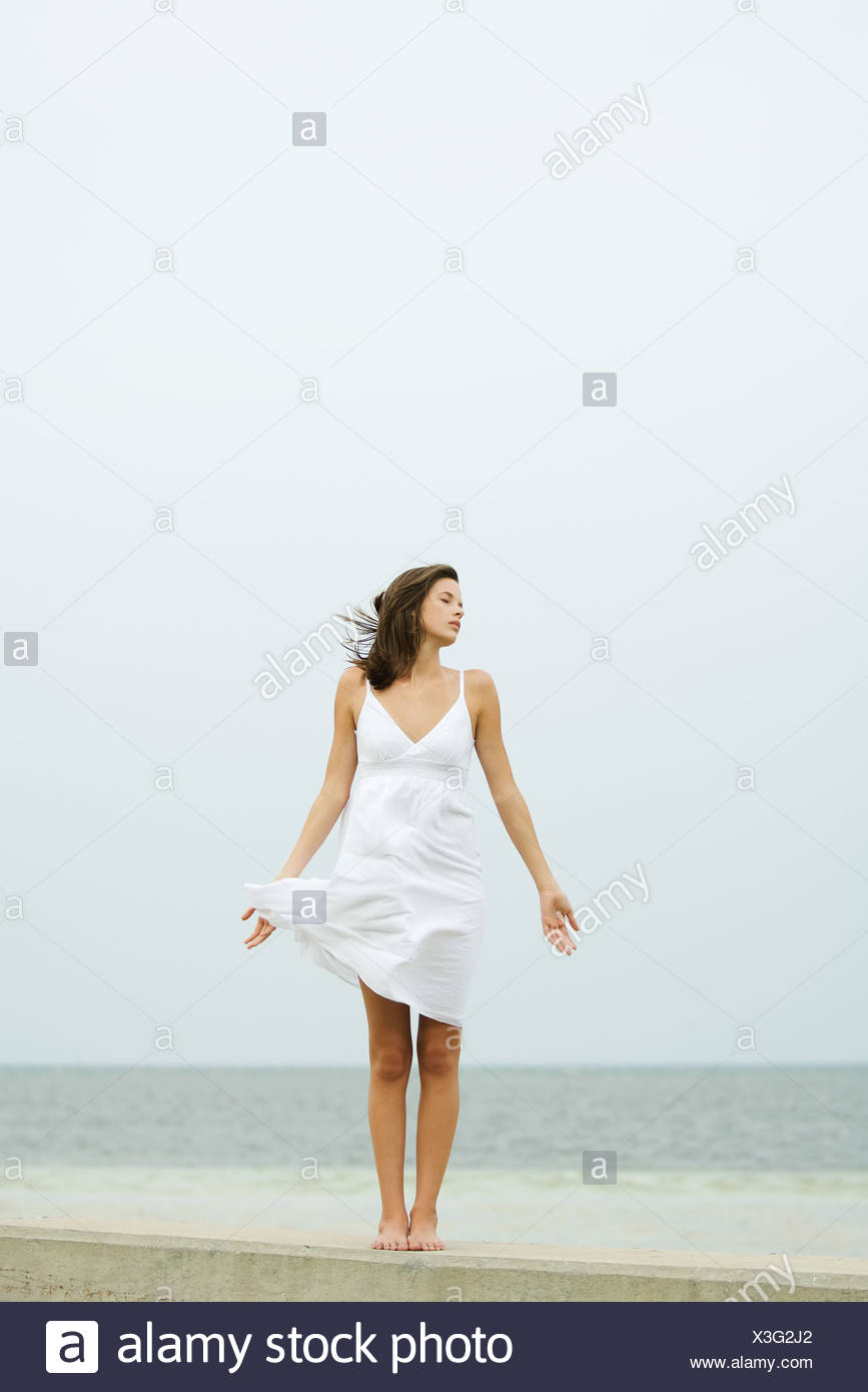 Teenage girl in sundress standing at the beach, tousled by wind, eyes closed - Stock Image