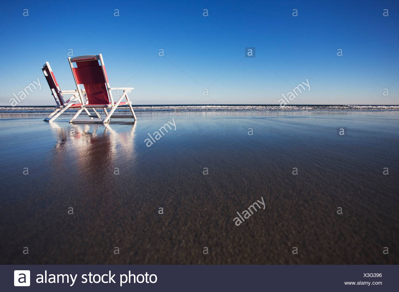 Two beach chairs on wet sand in York, Maine. - Stock Image
