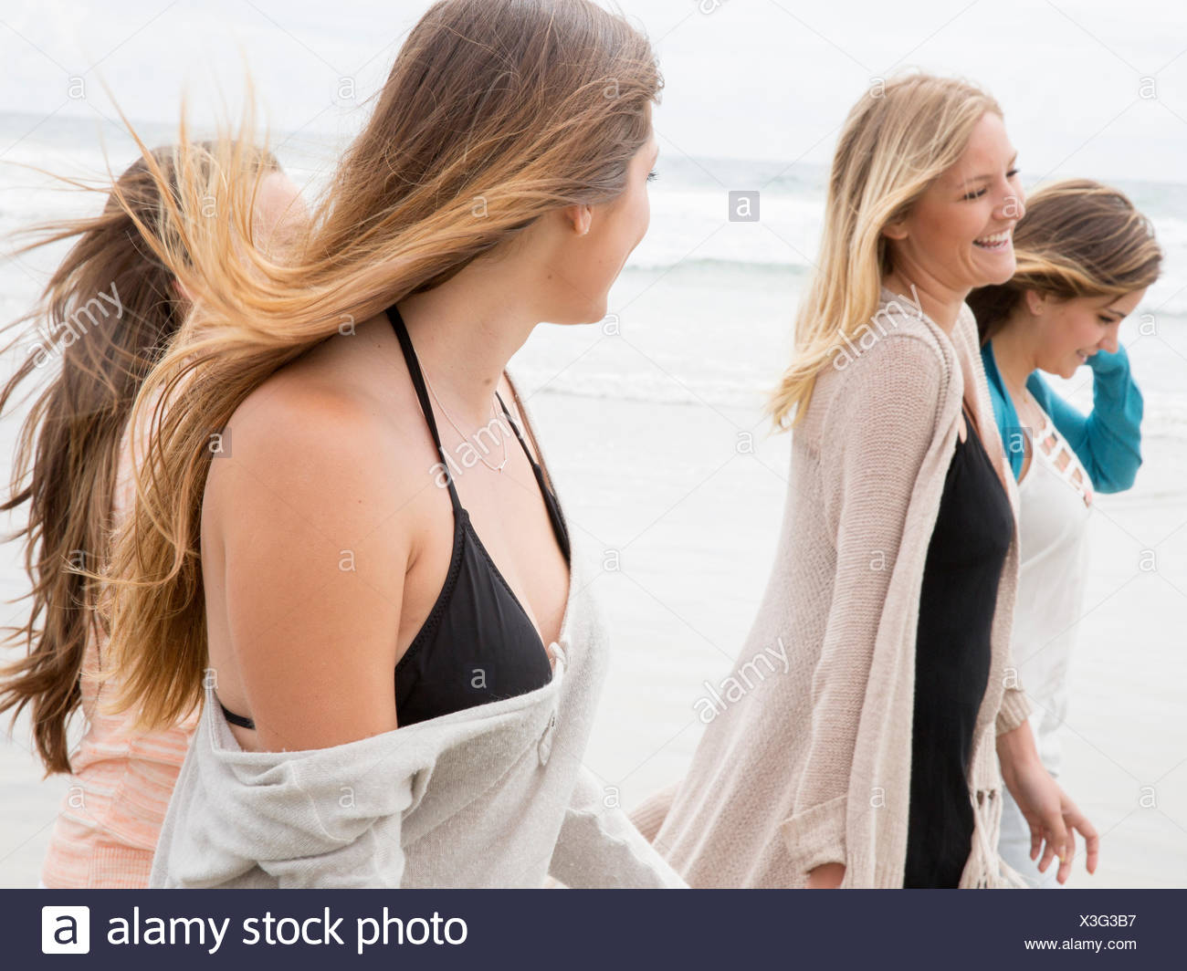 Four young women walking on a beach - Stock Image
