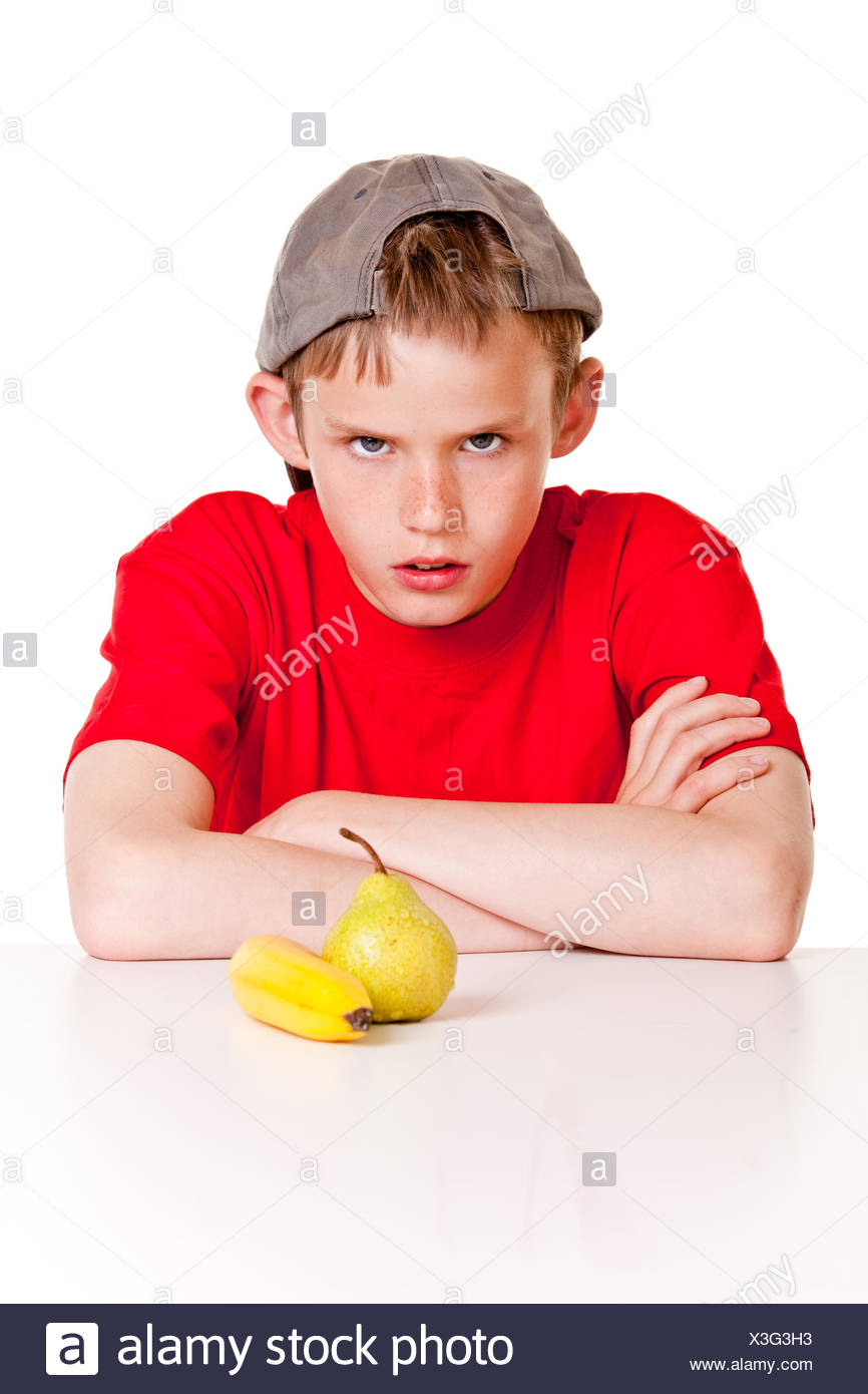 Defiant young boy glowering at the camera - Stock Image