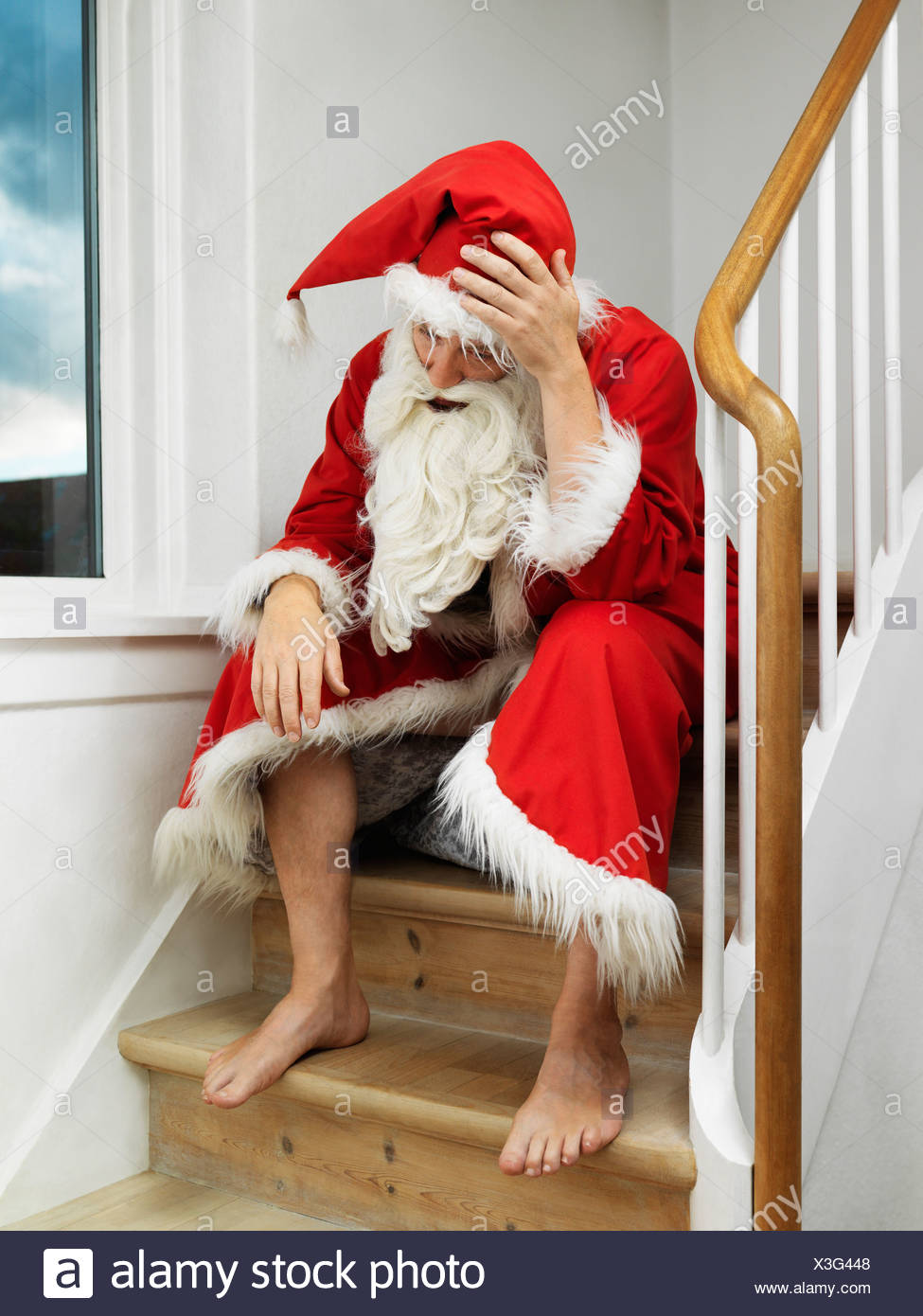 Man in Santa Claus suit sitting on steps - Stock Image