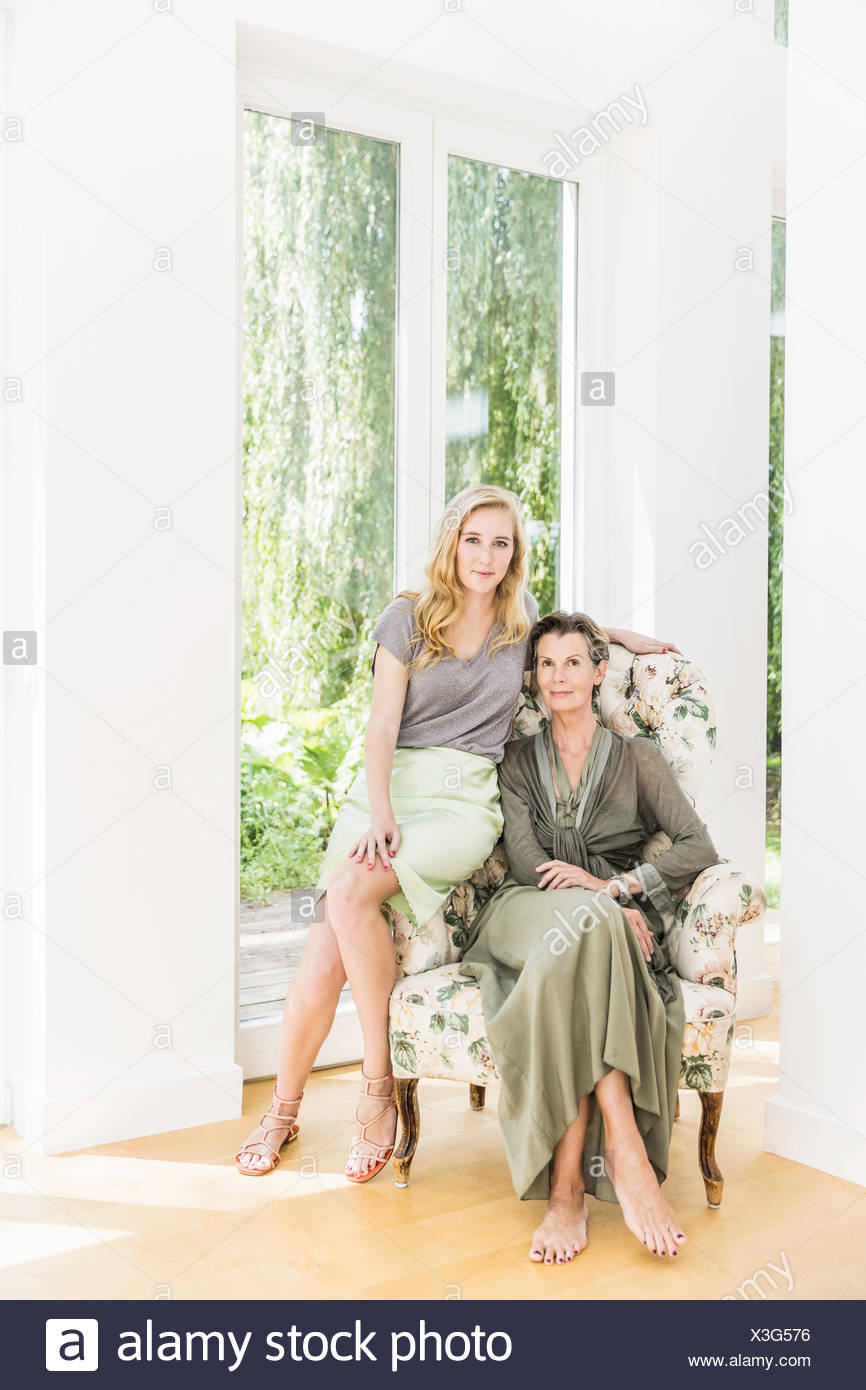 Portrait of senior woman and daughter sitting on armchair in living room Stock Photo