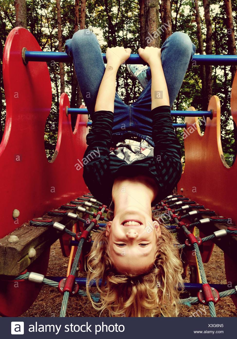 Portrait Of Happy Cute Girl Playing On Monkey Bars In Playground - Stock Image