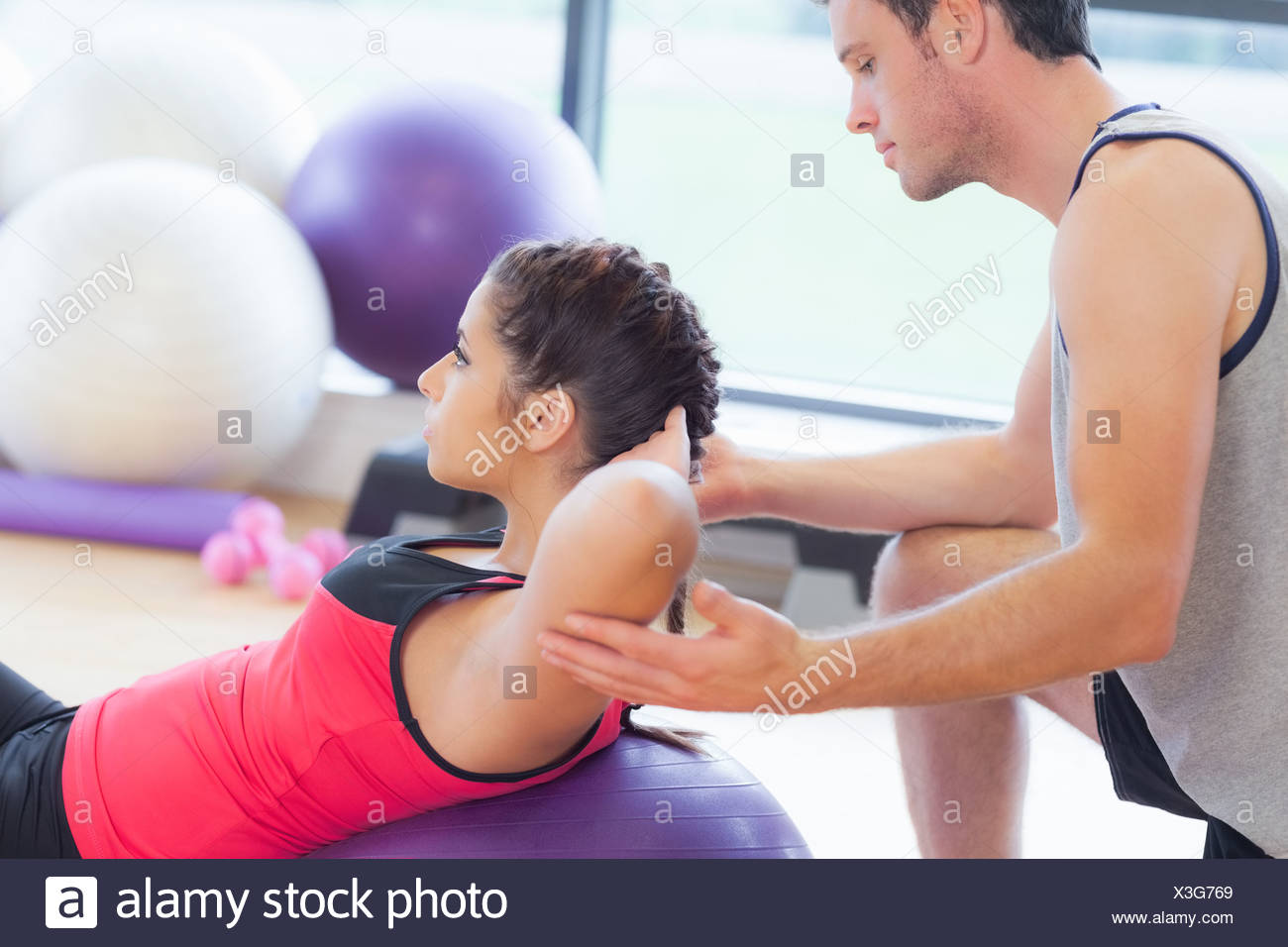 Male trainer helping woman do crunches  on fitness ball at gym - Stock Image