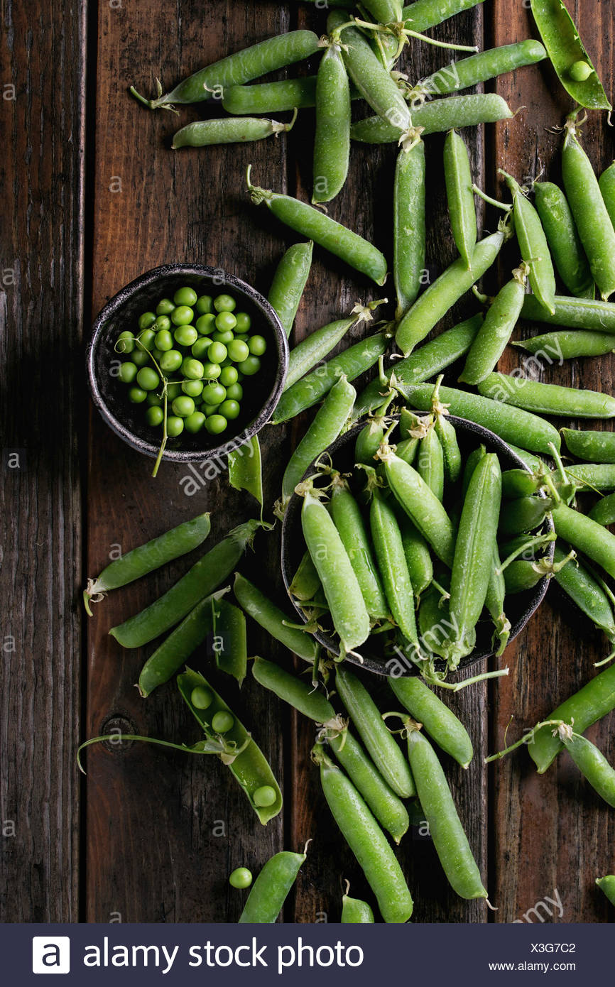 Young organic green pea pods and peas in bowls over old dark wooden planks background. Top view with space. Harvest, healthy eating. - Stock Image