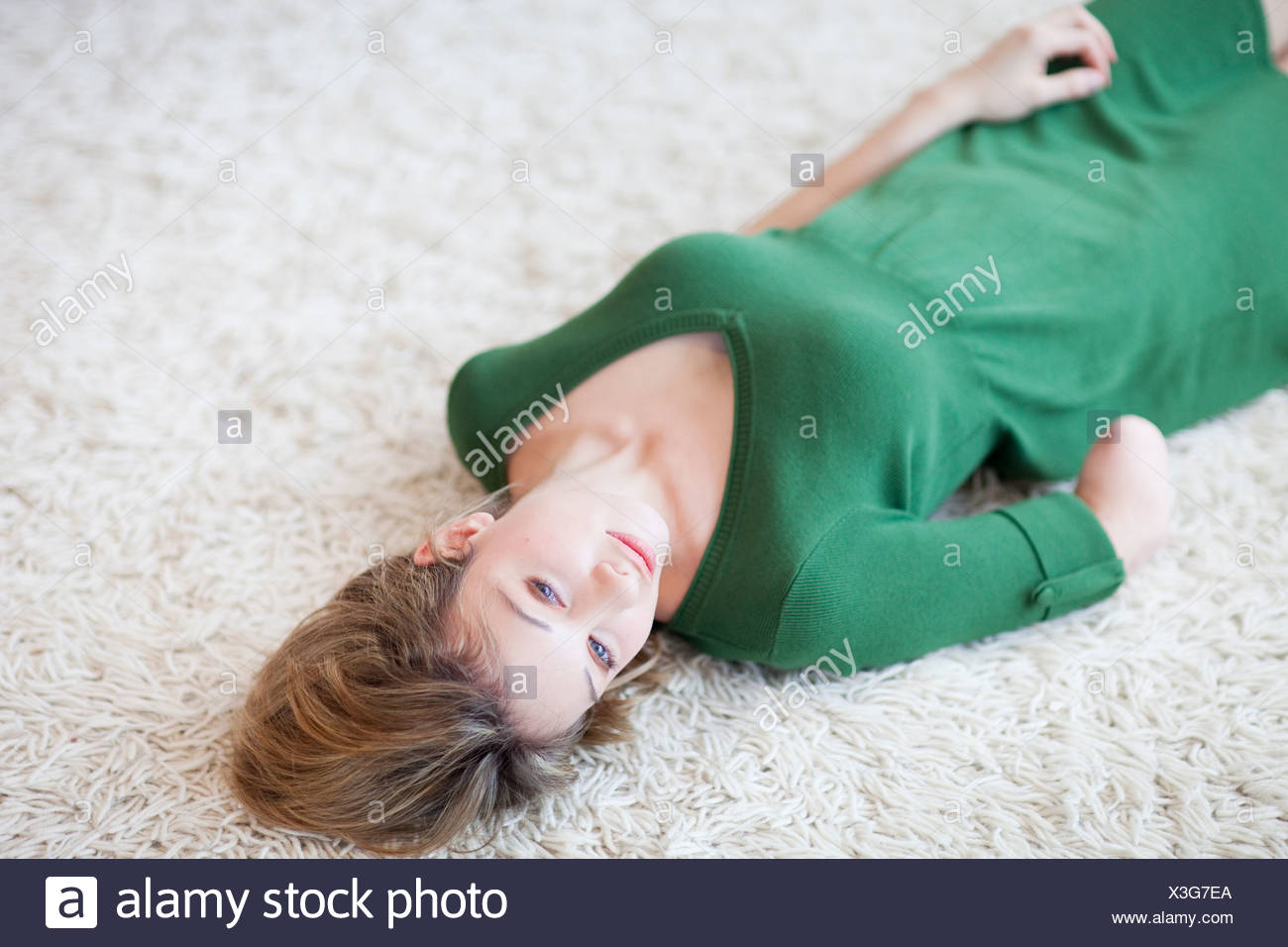 Young woman with amputee arm lying on carpet, high angle view - Stock Image