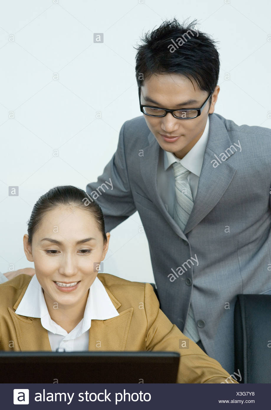 Businessman looking over female colleague's shoulder - Stock Image