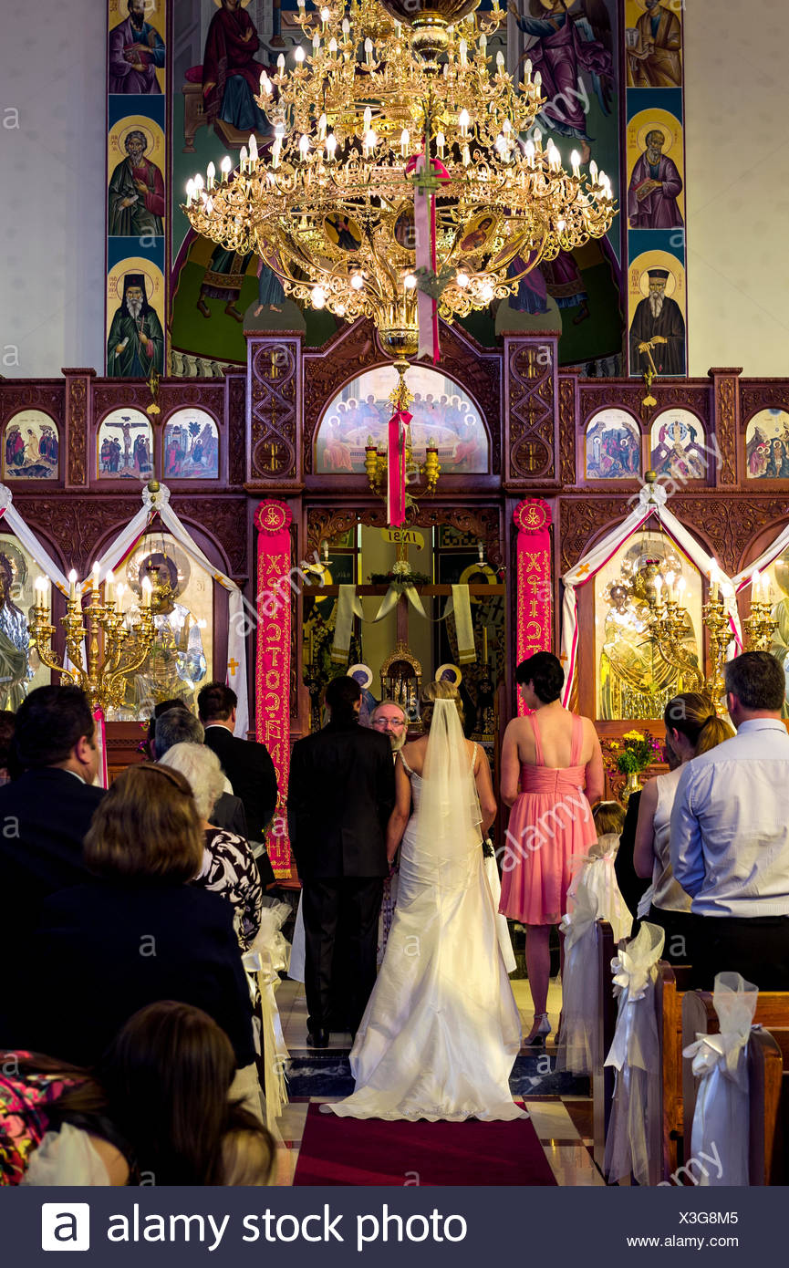 Guests join in prayers and celebrations at a Greek Orthodox wedding. - Stock Image