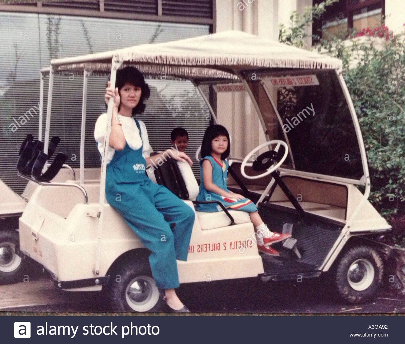 Woman Sitting In Golf Cart With Her Two Children - Stock Image
