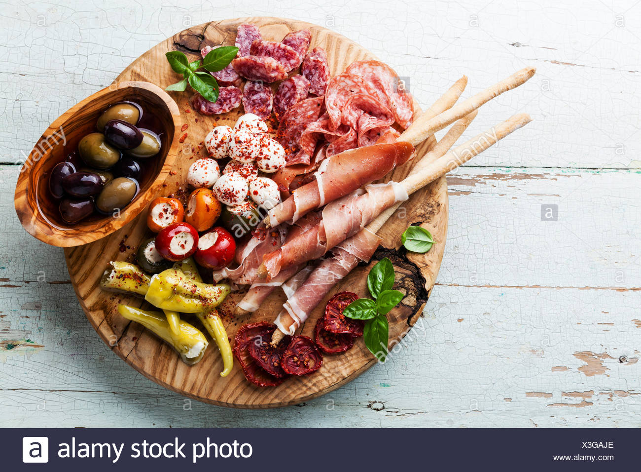 Antipasto Platter Cold meat plate with grissini bread sticks on wooden background - Stock Image
