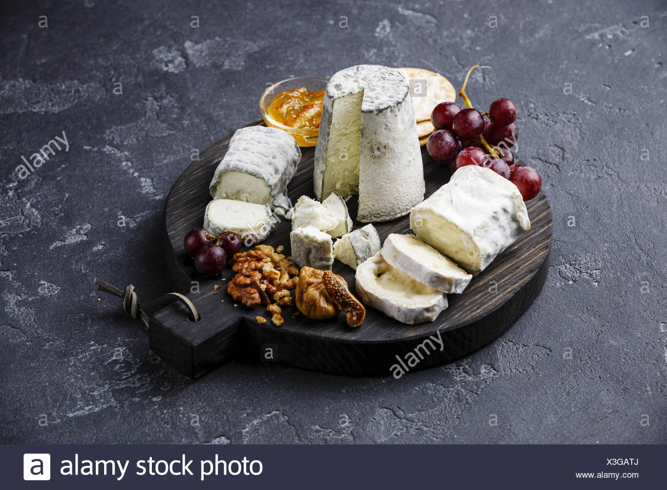 Goat Cheese board Snack assortment with confiture and grape on cutting board on black background - Stock Image