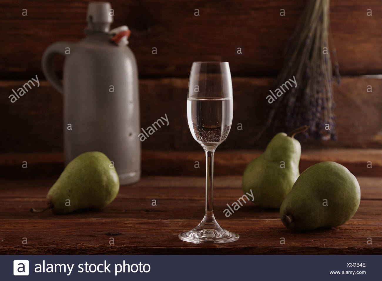 Glass of pear brandy with pears and a whiskey jar on a rustic wooden background - Stock Image
