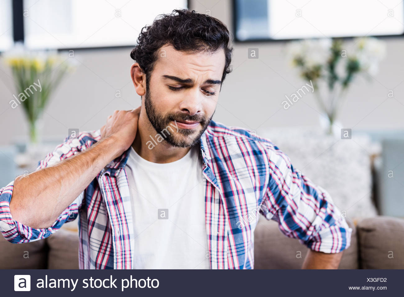 Suffering man with stiff neck - Stock Image